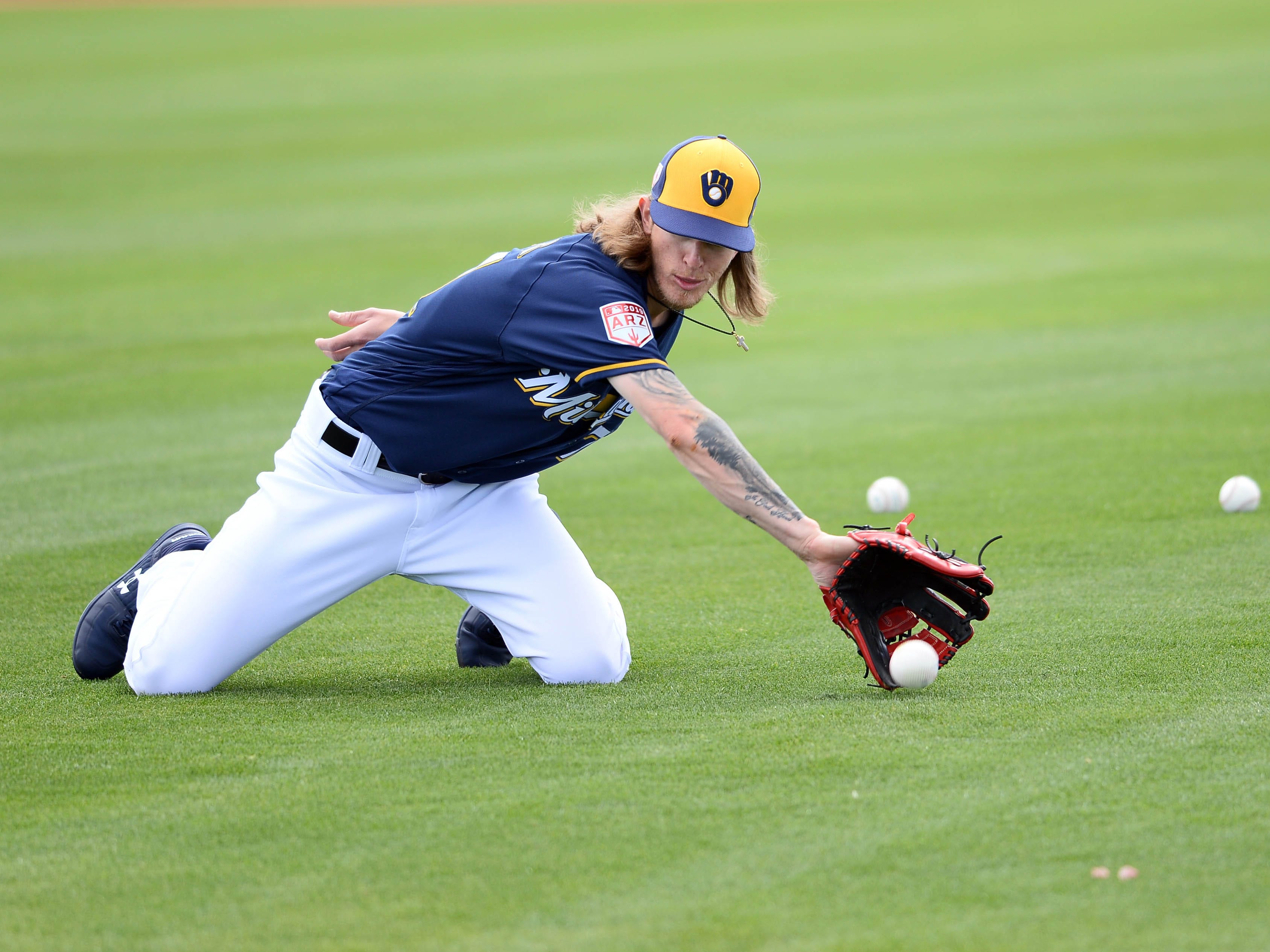 A kneeling Josh Hader gets ready to glove a ball during fielding drills Saturday.