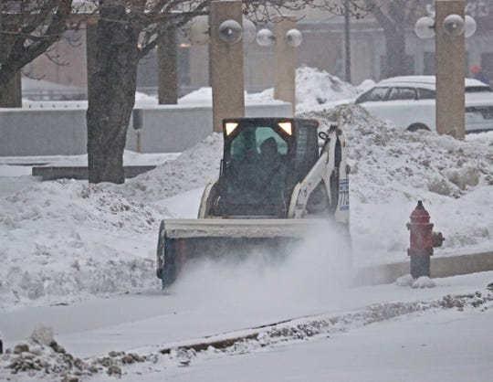 An all-wheel steer loader with a broom on the front clears the sidewalk along West Kilbourn Avenue near the Marcus Center on Sunday.