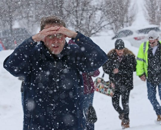Randy Medd of Oconomowoc shields his eyes from blowing snow as he makes his way from the parking lot to the Exposition Center at State Fair Park for the NARI Spring Home Improvement Show on Sunday.
