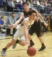 Izard County's Coby Everett drives around Calico Rock's Connor Sanders on Saturday night.