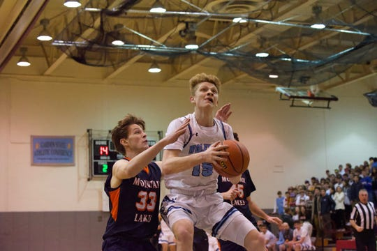 West Morris junior forward Ryan Hillier goes up for a shot, guarded by Mountain Lakes senior Jack Baker, during a Morris County Tournament boys basketball semifinal.