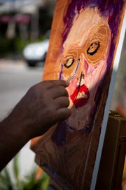 Ken Fraser works on a painting during the annual Third on Canvas event on Third Street South in Naples, on Sunday, Feb. 17, 2019.