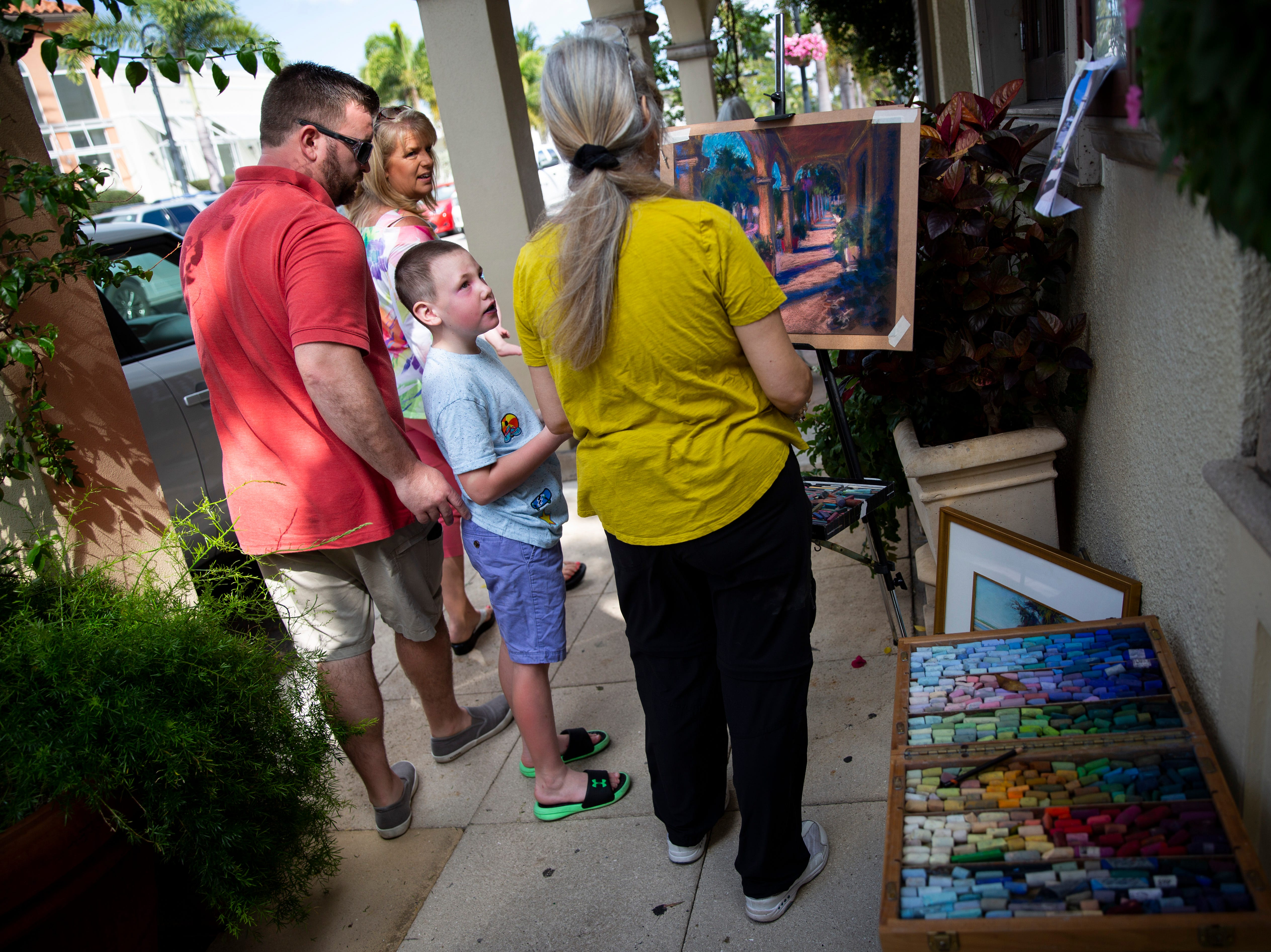 """Dawson George, 7, stops to talk to Cheri Dunnigan as she works on her chalk pastel drawing during the annual Third on Canvas event on Third Street South in Naples on Sunday, Feb. 17, 2019. """"How'd you do that?"""" asked Dawson, who was very impressed by the artwork."""