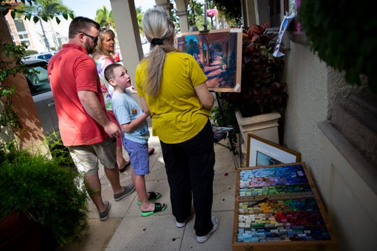 "Dawson George, 7, stops to talk to Cheri Dunnigan as she works on her chalk pastel drawing during the annual Third on Canvas event on Third Street South in Naples on Sunday, Feb. 17, 2019. ""How'd you do that?"" asked Dawson, who was very impressed by the artwork."