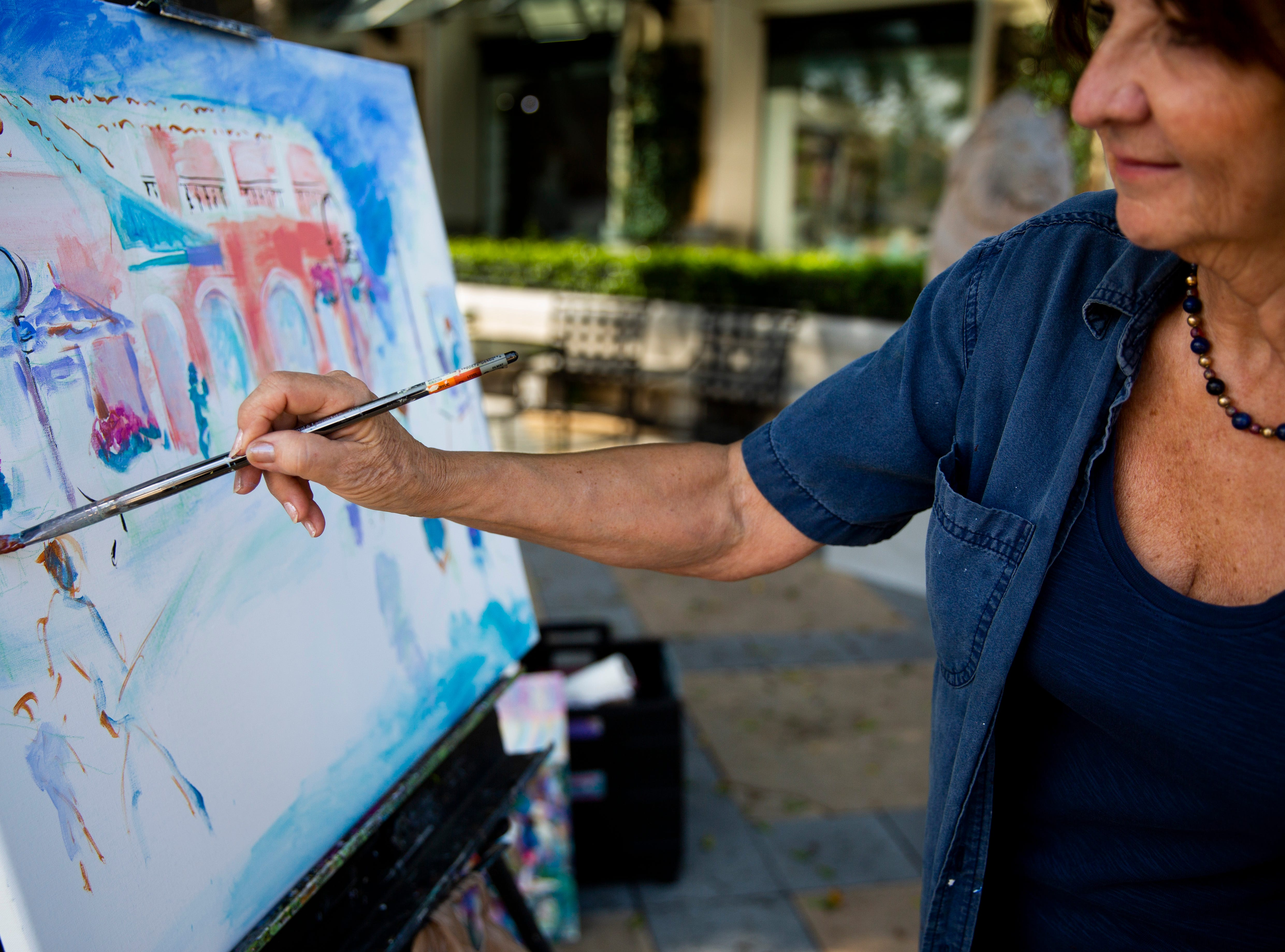 Janine Wesselmann paints during the annual Third on Canvas event on Third Street South in Naples on Sunday, Feb. 17, 2019. Wesselmann has been participating in Third on Canvas for the past 11 years.