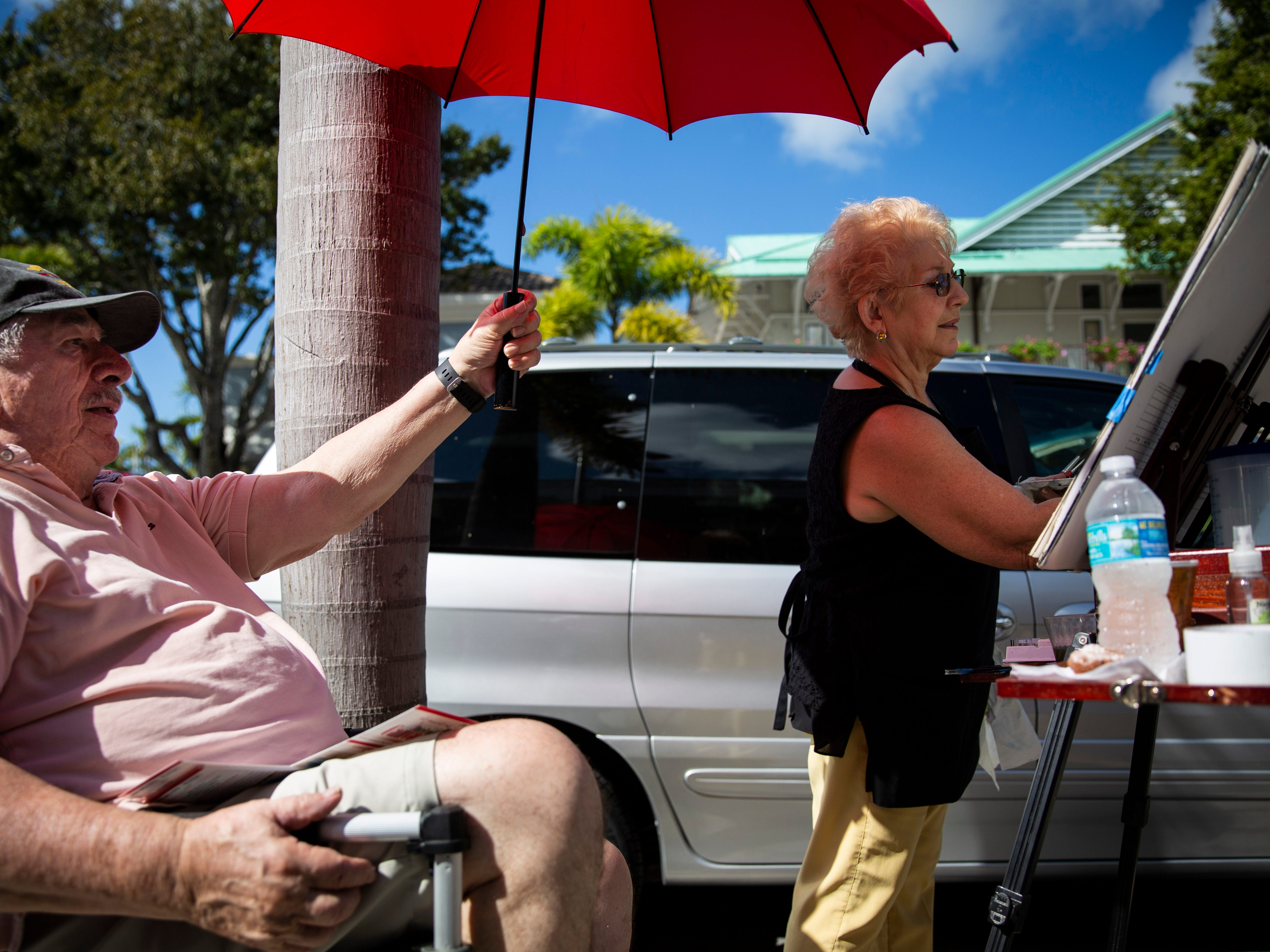 """Terry Hewitt holds an umbrella over his wife, Teresa Hewitt, while she paints during the annual Third on Canvas event on Third Street South in Naples, on Sunday, Feb. 17, 2019. The Hewitts recently celebrated their 50th wedding anniversary. """"I haven't been doing this for 50 years,"""" Terry said, gesturing toward the umbrella, """"my arm would fall off."""""""