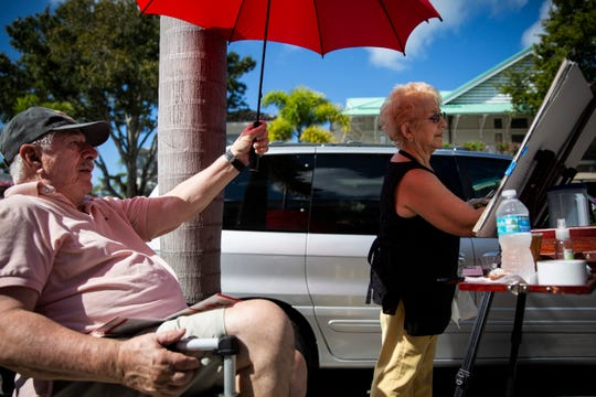 "Terry Hewitt holds an umbrella over his wife, Teresa Hewitt, while she paints during the annual Third on Canvas event on Third Street South in Naples, on Sunday, Feb. 17, 2019. The Hewitts recently celebrated their 50th wedding anniversary. ""I haven't been doing this for 50 years,"" Terry said, gesturing toward the umbrella, ""my arm would fall off."""