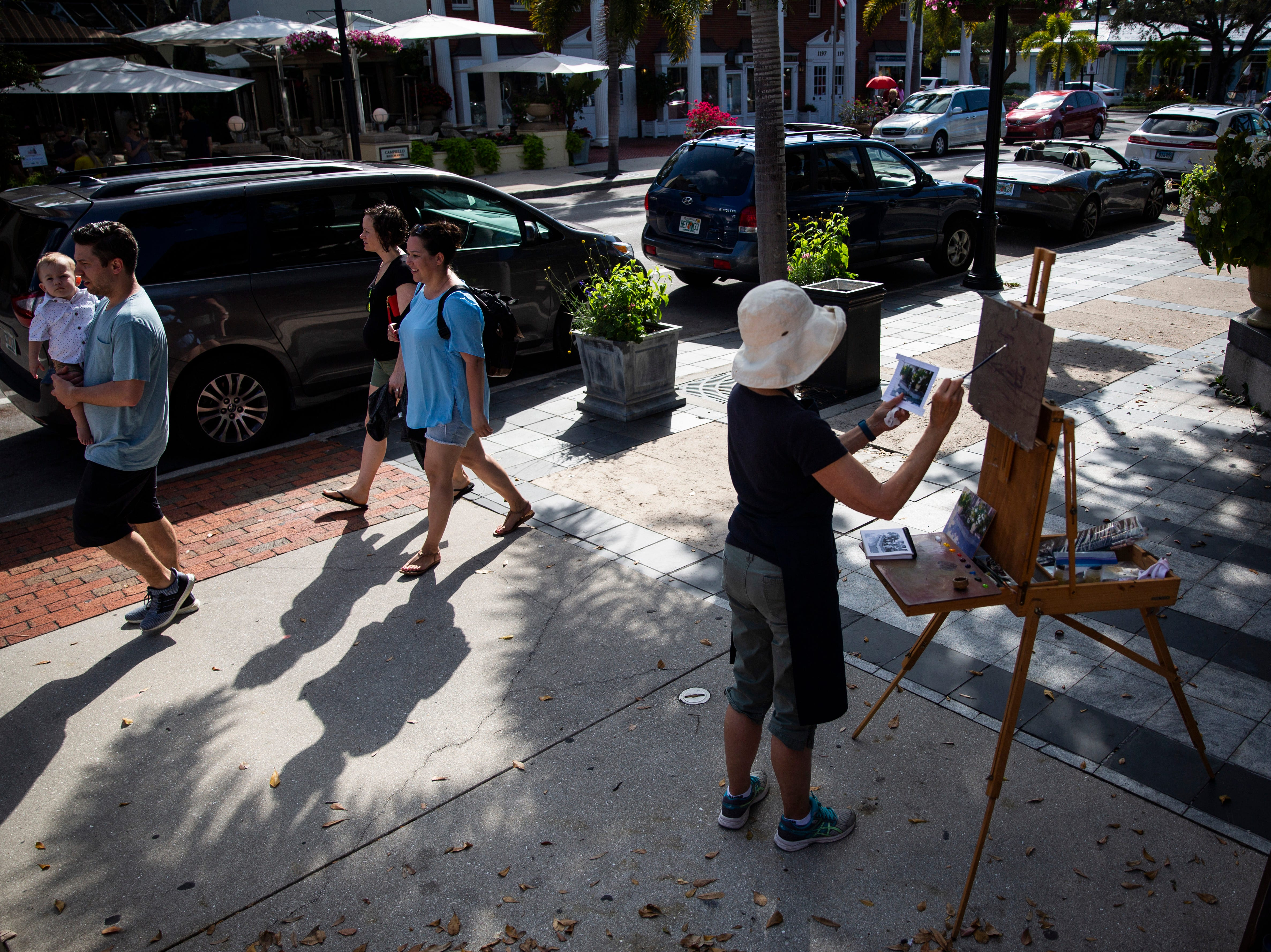Susan Lindsey paints while people walk past her during the annual Third on Canvas event on Third Street South in Naples, on Sunday, Feb. 17, 2019.