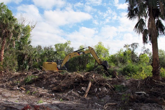 An excavator clears trees and brush from acreage along Manatee Road in January 2019 in preparation to build Journey's End townhome community.