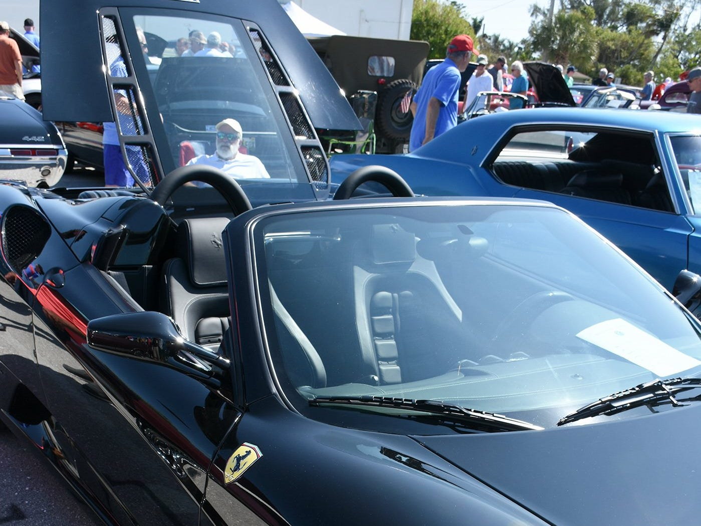 Craig Bagin is framed in the transparent rear deck of his Ferrari F-430. The annual Kiwanis car show brought 170 collectible cars and thousands of car enthusiasts to Veterans Community Park on Marco Island Sunday.