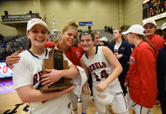 Michelle Sidor (no.23) Of Saddle River Day holds the championship trophy as she has photos taken together with her teammates Jenna Jordan (no.33) and Jordan Janowski (no.14) following their victory 55 to 49 over Immaculate Heart Academy during the Bergen County girls basketball final at Ramapo College in Mahwah on 02/17/19.