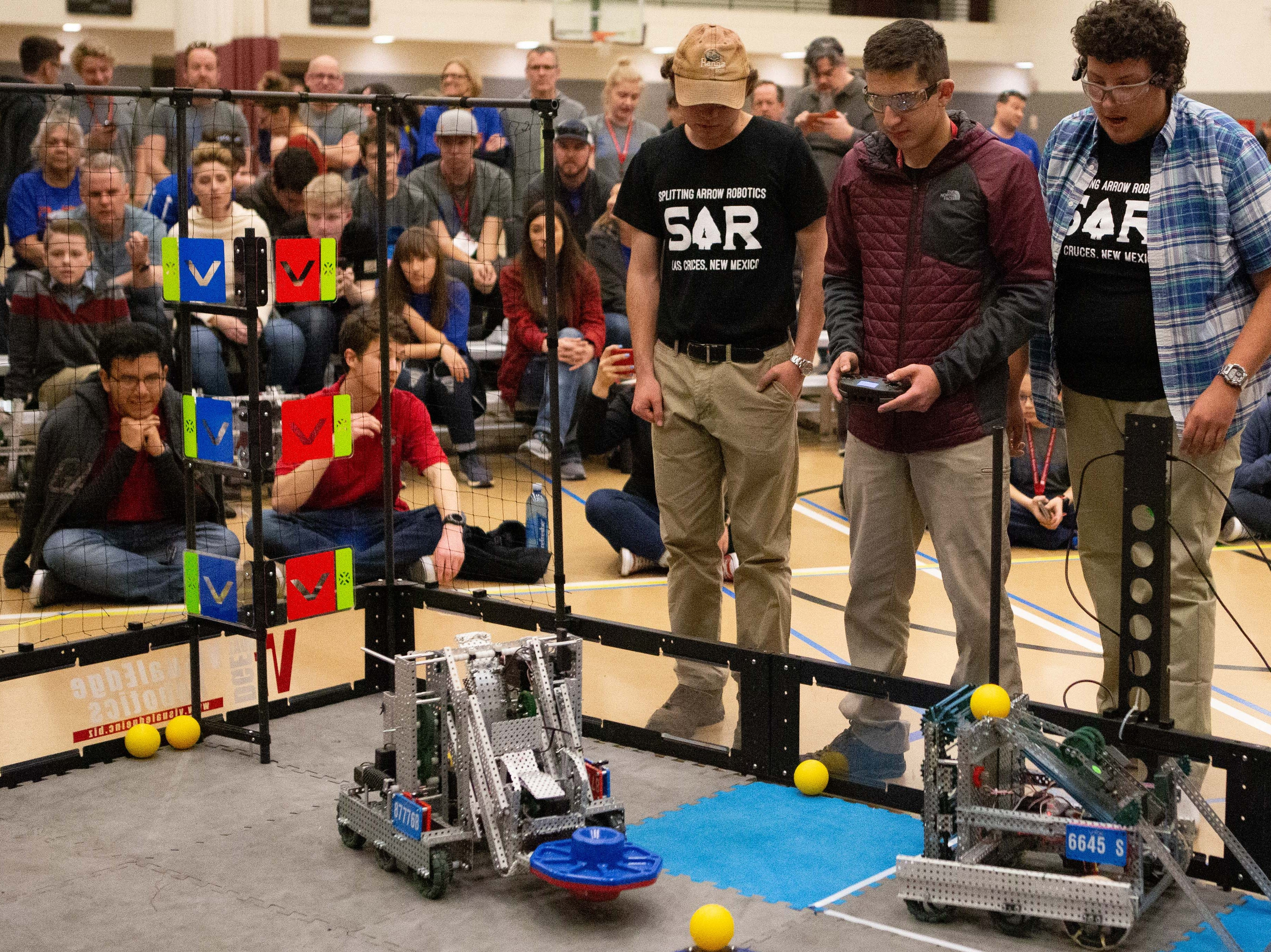 Splitting Arrow Robotics team, from left, John Bell, 17, Shiloh Payne, 18, and Brenton Candelaria, 18 at the VEX Robotics competition for elementary, middle and high school students, held on the NMSU campus on Saturday, Feb. 16, 2019.