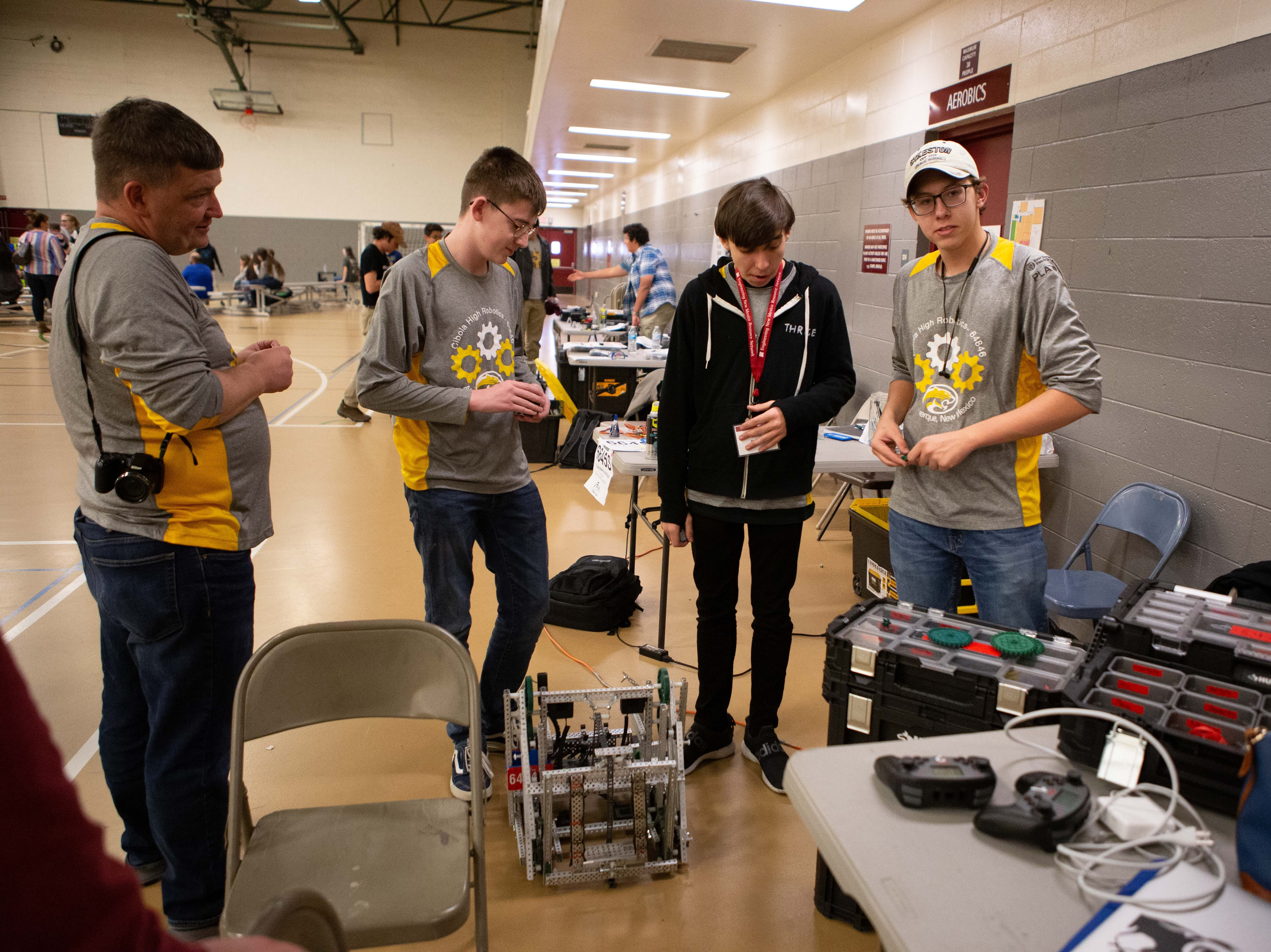 Cibola High School's team, from right, is Connor Giese, 16, Noah Fry, 16, and Evan De Buck, 16. Father Peter De Buck is at far left. The team was one of two that that prevailed in the VEX Robotics competition Saturday, Feb. 16, 2019.