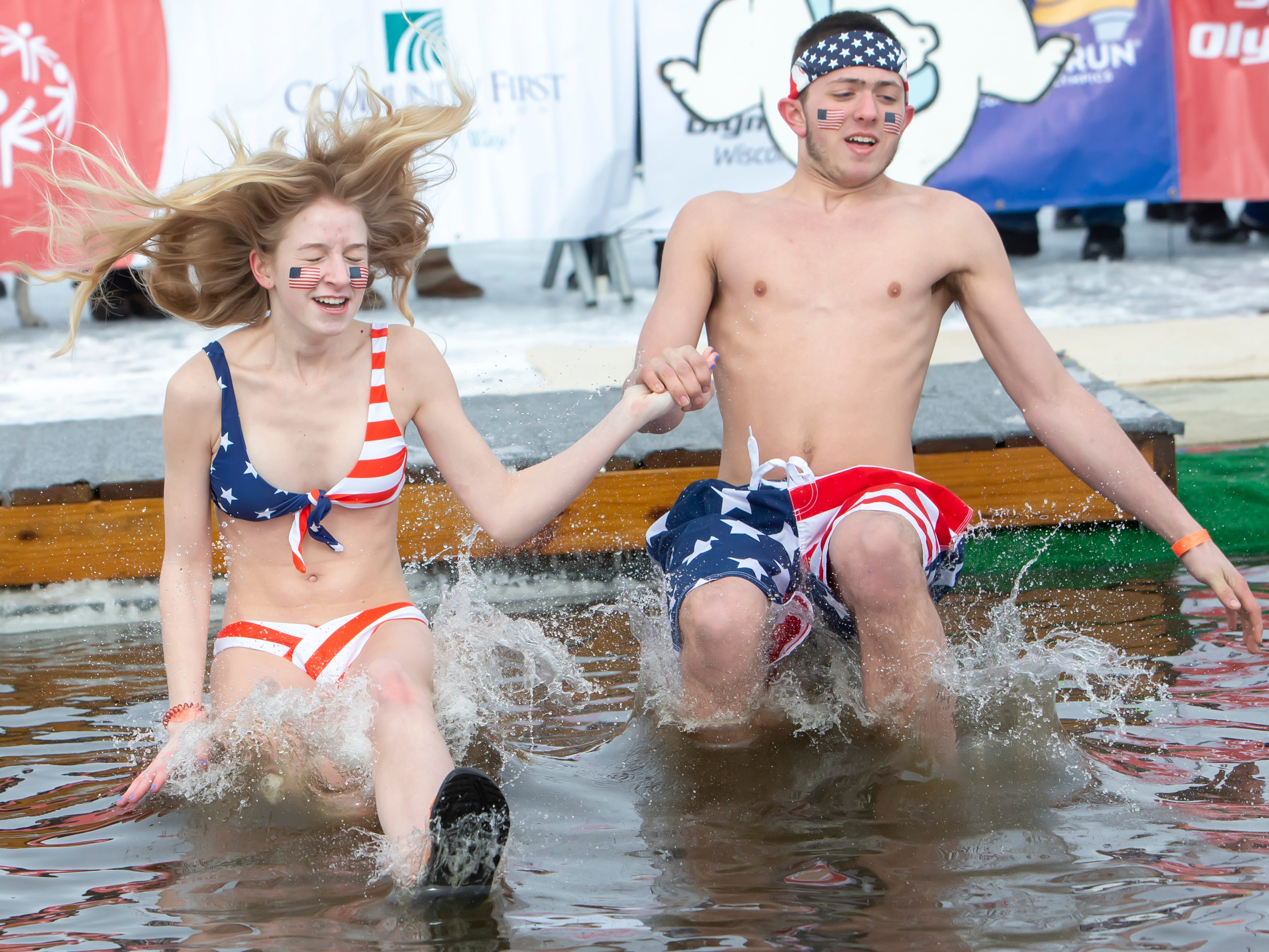 A patriotic couple plunge together during the Special Olympics Wisconsin Polar Plunge in Oshkosh, Wis., on Saturday, February 16, 2019, at Miller's Bay in Menominee Park.