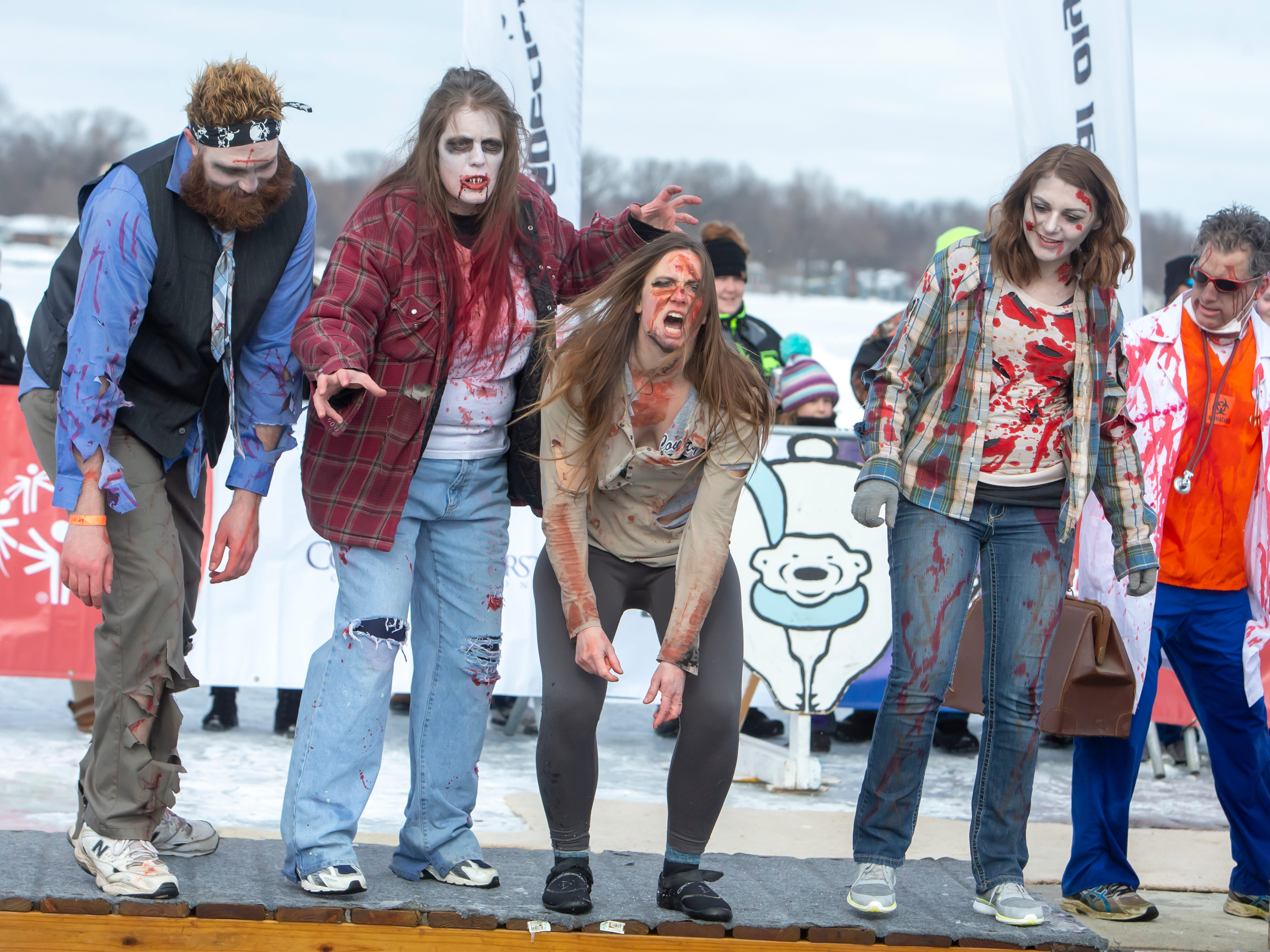 People dressed as zombies get ready to take the jump during the Special Olympics Wisconsin Polar Plunge in Oshkosh, Wis., on Saturday, February 16, 2019, at Miller's Bay in Menominee Park.