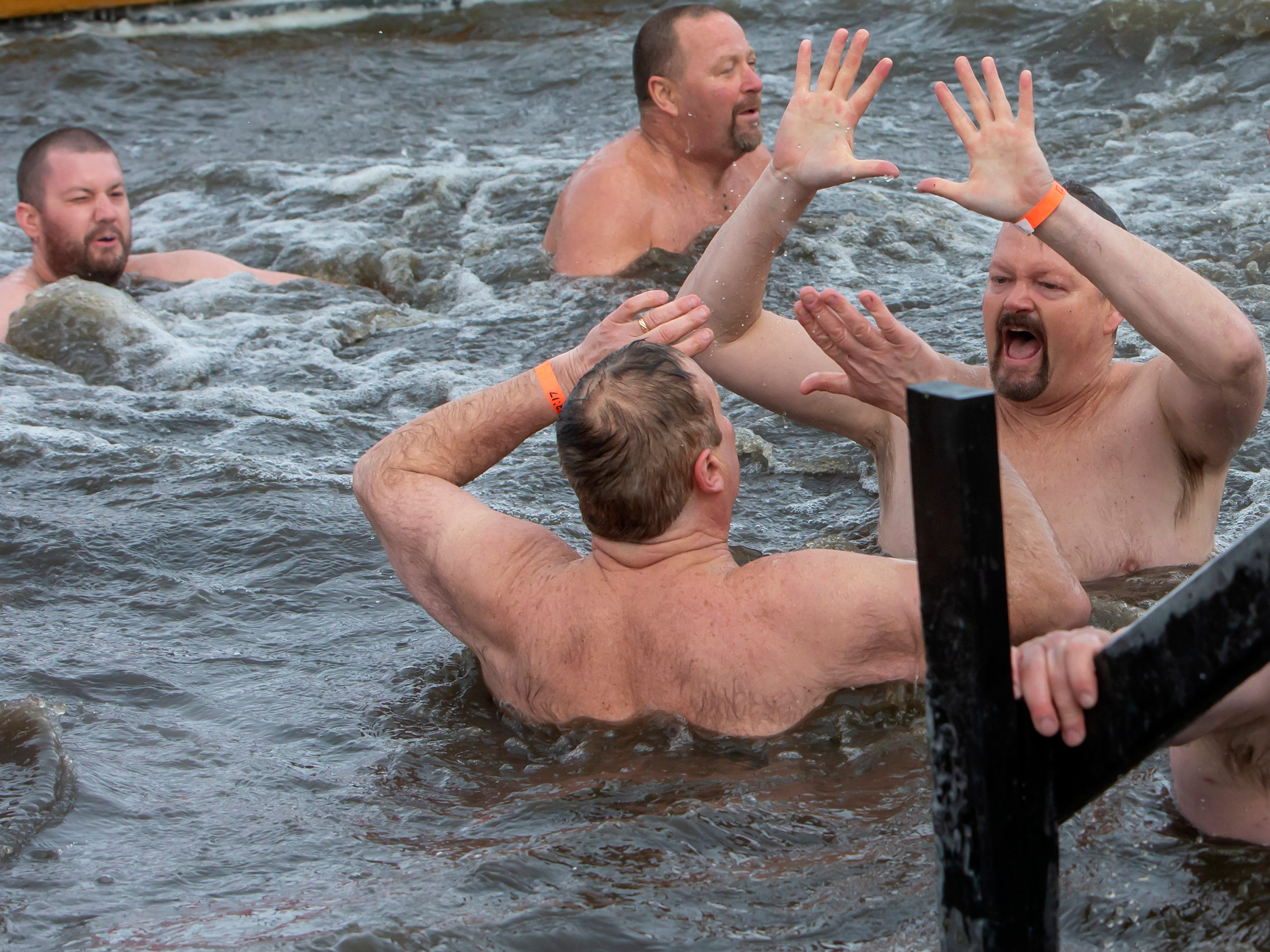 People react while in the cold water during the Special Olympics Wisconsin Polar Plunge in Oshkosh, Wis., on Saturday, February 16, 2019, at Miller's Bay in Menominee Park.
