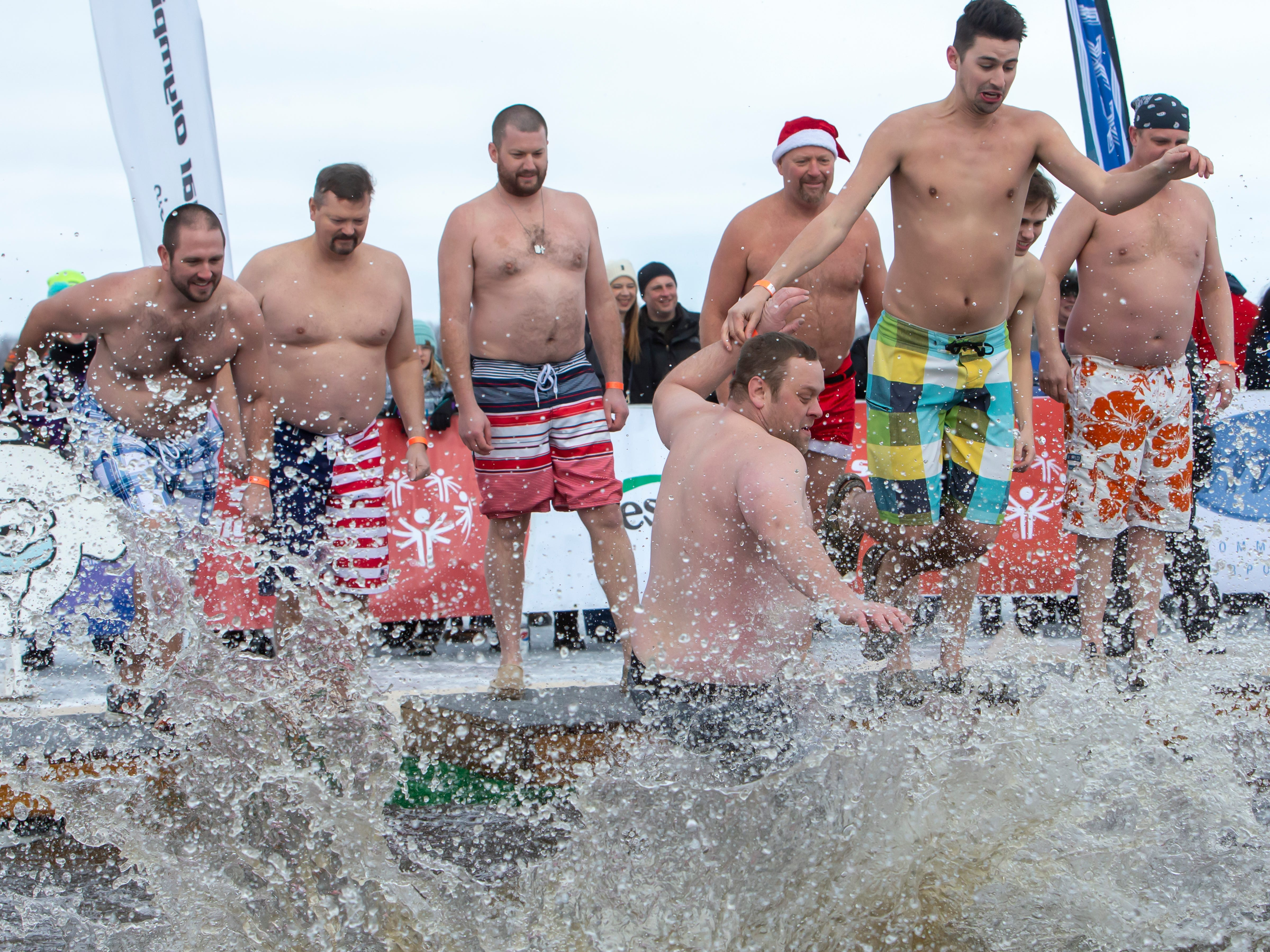 Groups of people jump together during the Special Olympics Wisconsin Polar Plunge in Oshkosh, Wis., on Saturday, February 16, 2019, at Miller's Bay in Menominee Park.