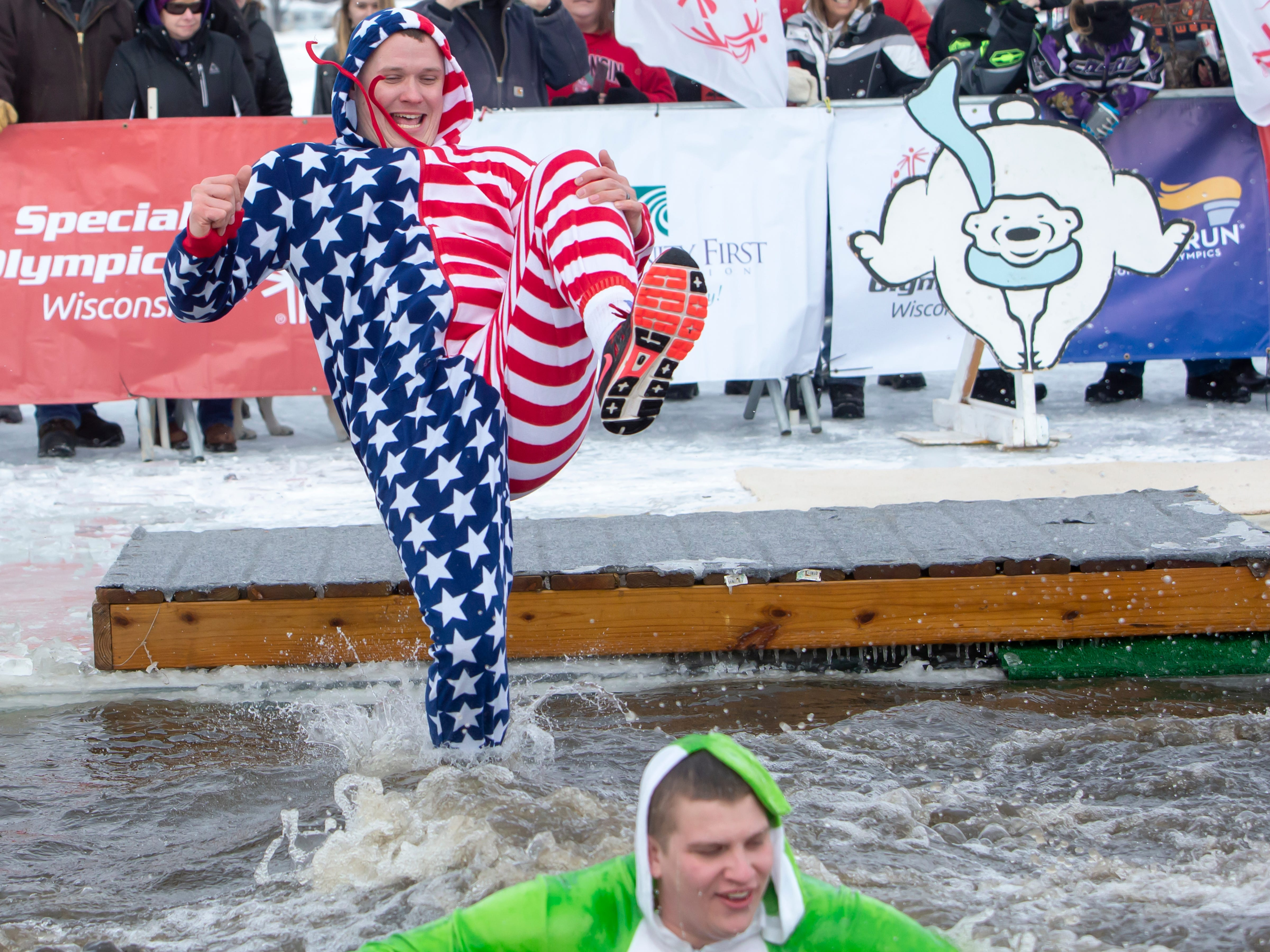 People react while entering the freezing water during the Special Olympics Wisconsin Polar Plunge in Oshkosh, Wis., on Saturday, February 16, 2019, at Miller's Bay in Menominee Park.