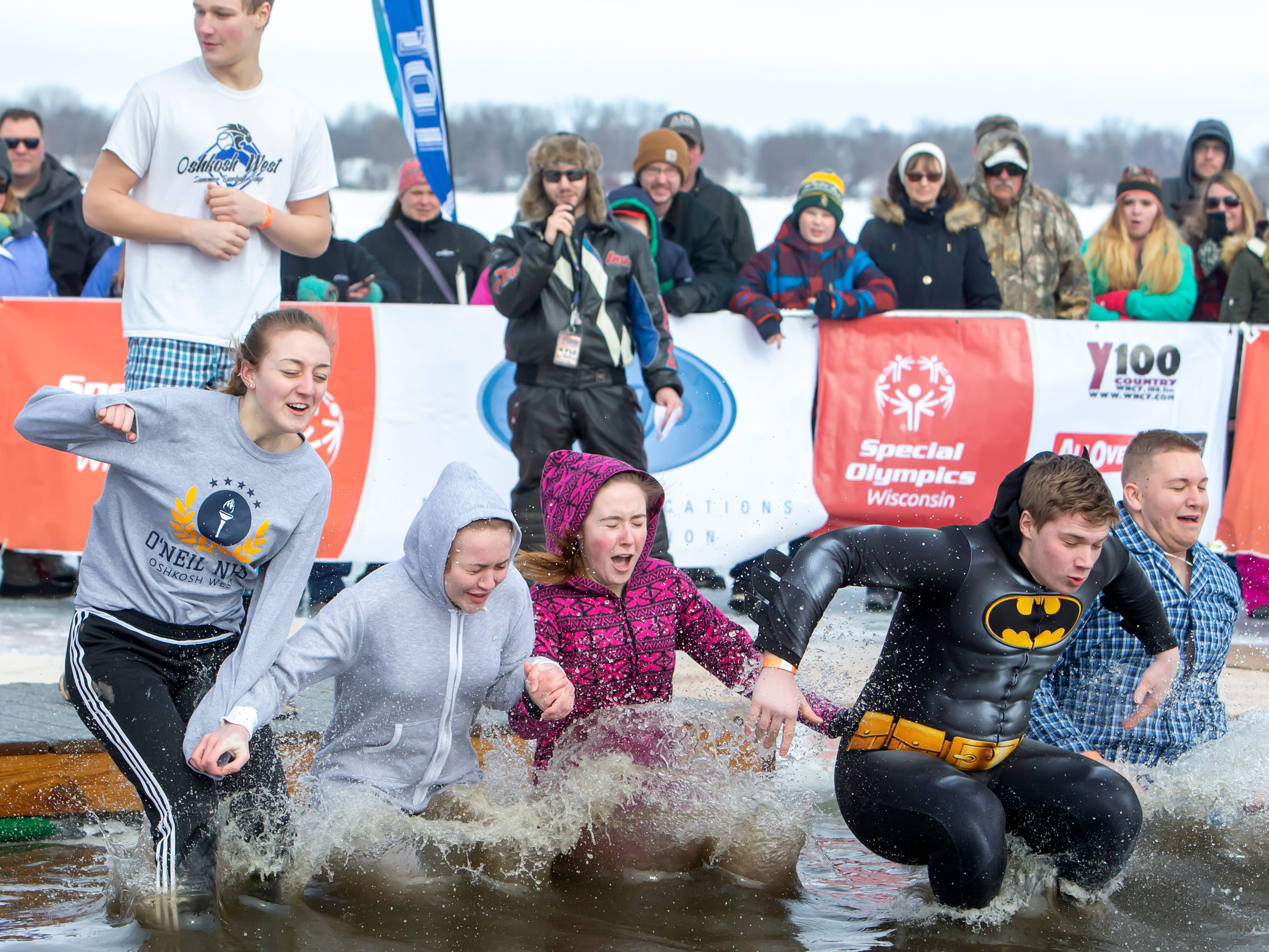 Oshkosh West High School students make the jump during the Special Olympics Wisconsin Polar Plunge in Oshkosh, Wis., on Saturday, February 16, 2019, at Miller's Bay in Menominee Park.