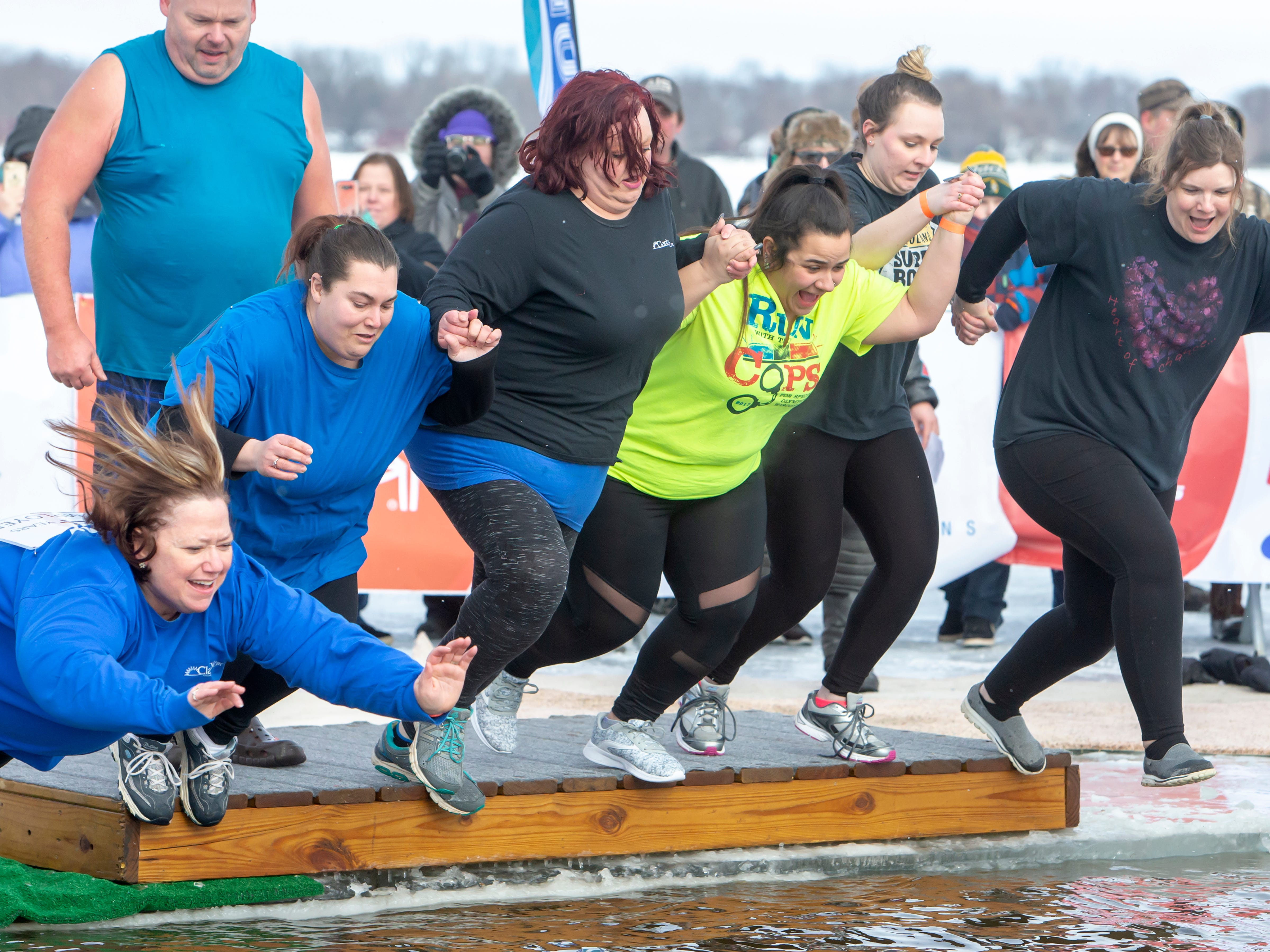 Clarity Care employees jump into the cold water during the Special Olympics Wisconsin Polar Plunge in Oshkosh, Wis., on Saturday, February 16, 2019, at Miller's Bay in Menominee Park.