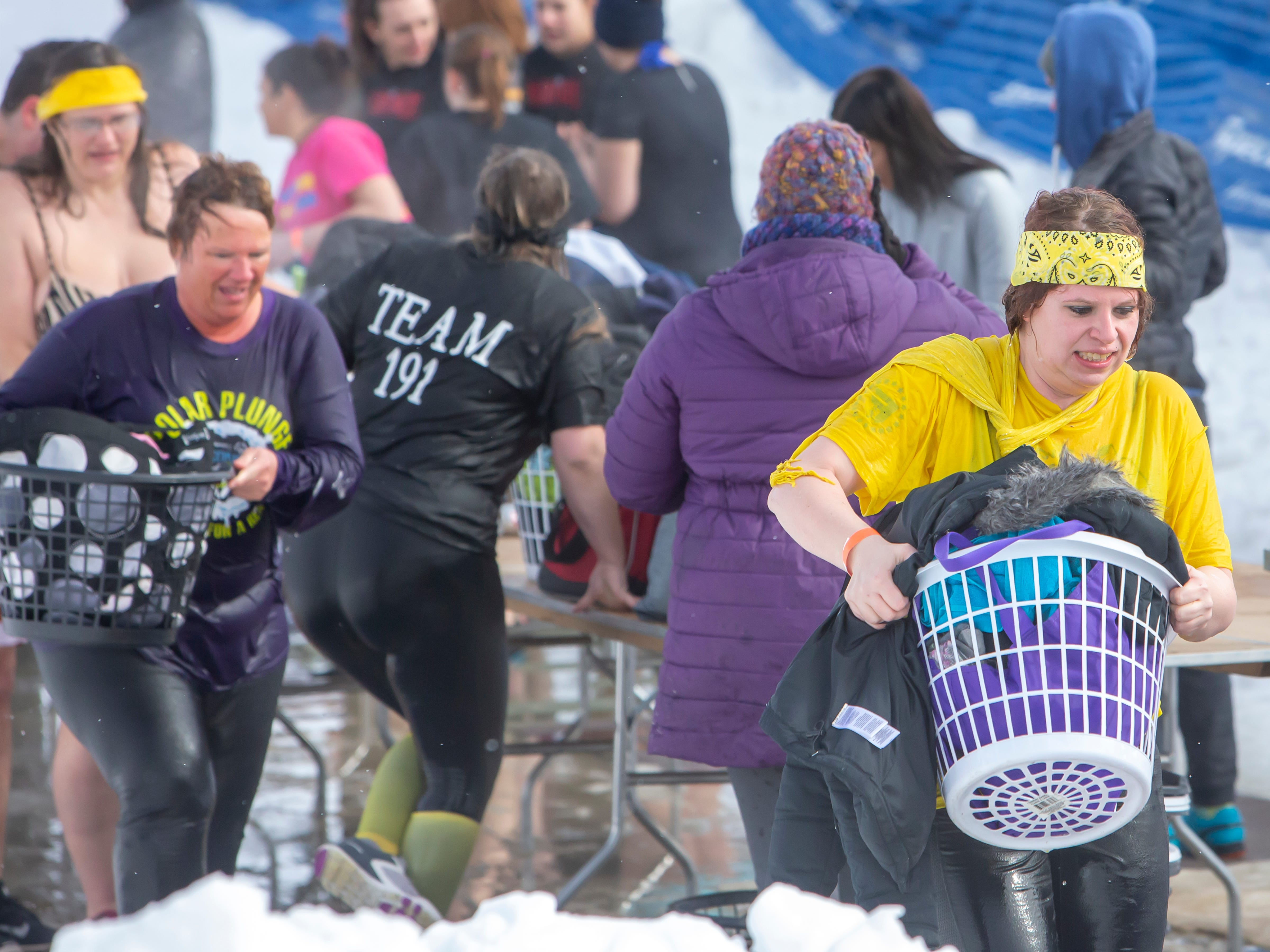 Participants hurry to a warmer spot after their plunge during the Special Olympics Wisconsin Polar Plunge in Oshkosh, Wis., on Saturday, February 16, 2019, at Miller's Bay in Menominee Park.