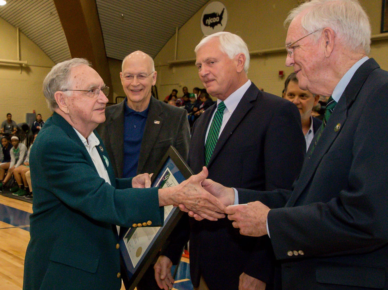 Gerald McArthur, left, accepts Pensacola State College's inaugural Athletics Hall of Fame awards for his late brother Gerald, who was a 1953 graduate of the college, on Saturday, February 16, 2019.
