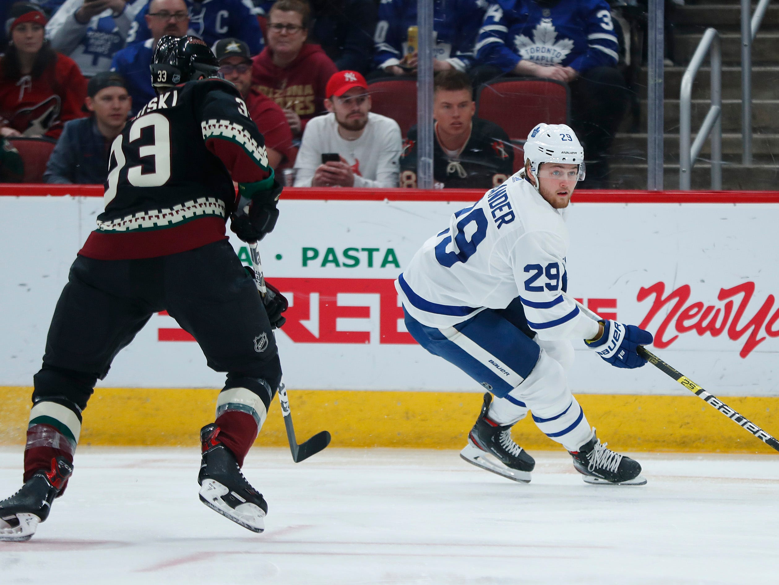 Maple Leafs' William Nylander (29) looks for teammates against a charging Coyotes' Alex Goligoski (33) during the first period at Gila River Arena in Glendale, Ariz. on February 16, 2019.