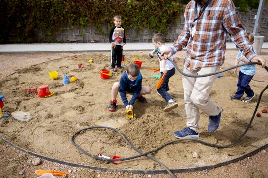 Kids play in the sand that Program  Assistant  John Bello spay with water at the Desert Botanical Garden 80th Anniversary Celebration on Saturday, Feb. 26, 2019. From left, Charlie Guminiak, Bentley Pagel, Greyson Walsh and Kellen Walsh play in the area.