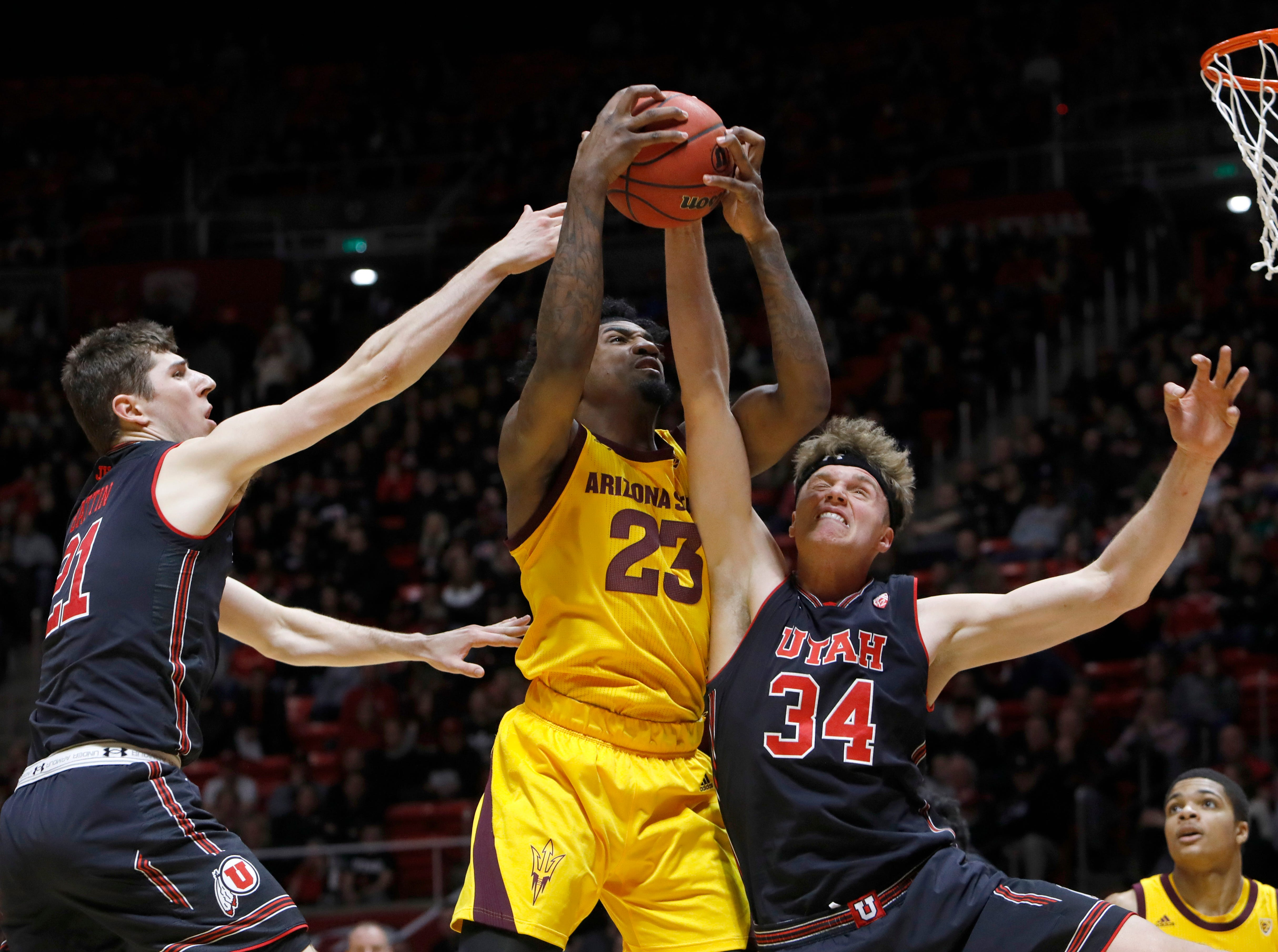 Utah's Riley Battin (21) and Jayce Johnson (34) compete with Arizona State's Romello White (23) for a rebound during the first half of an NCAA college basketball game Saturday, Feb. 16, 2019, in Salt Lake City. (AP Photo/Kim Raff)