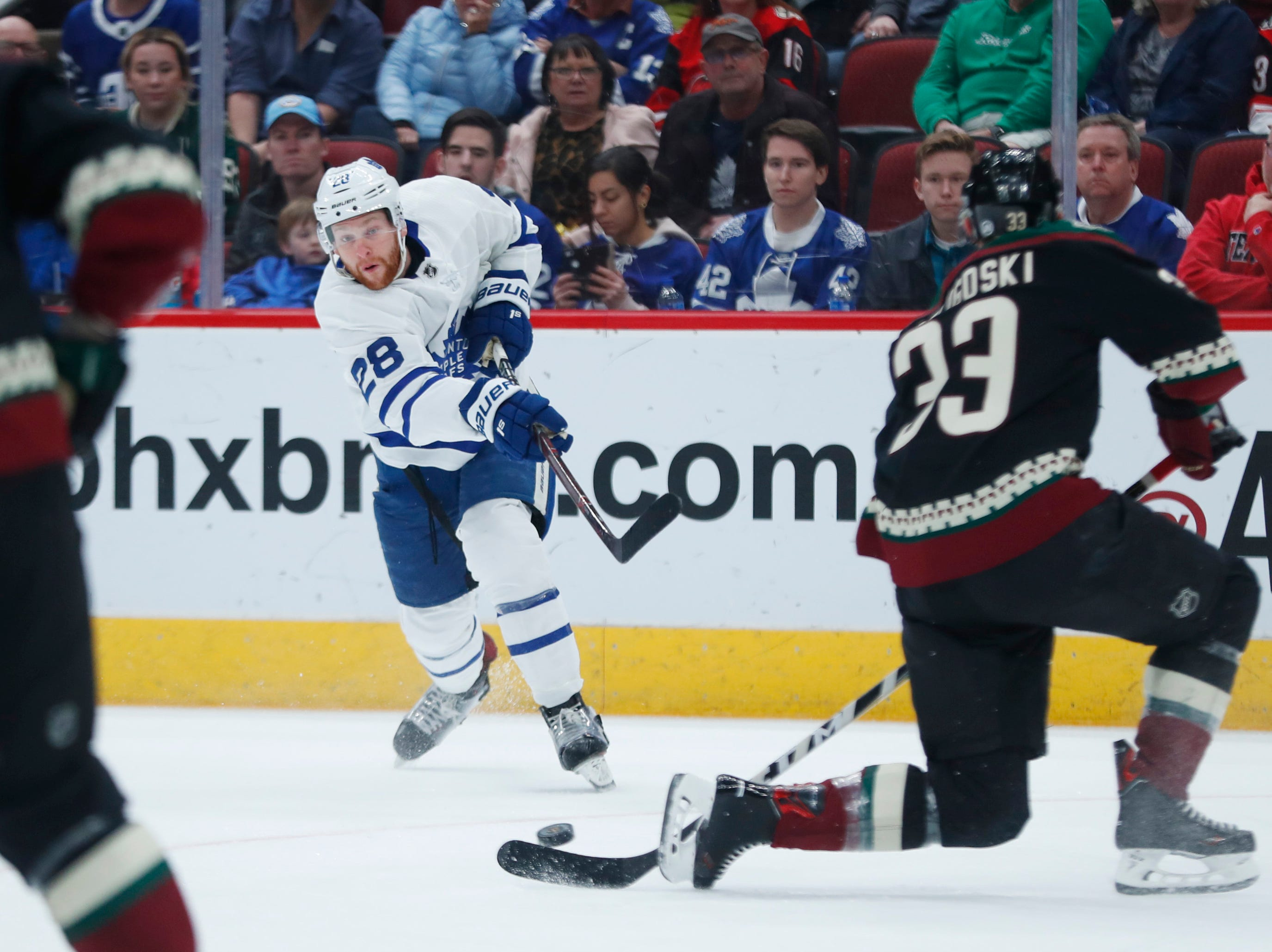 Maple Leafs' Connor Brown (28) shoots against Coyotes' Alex Goligoski (33) during the first period at Gila River Arena in Glendale, Ariz. on February 16, 2019.