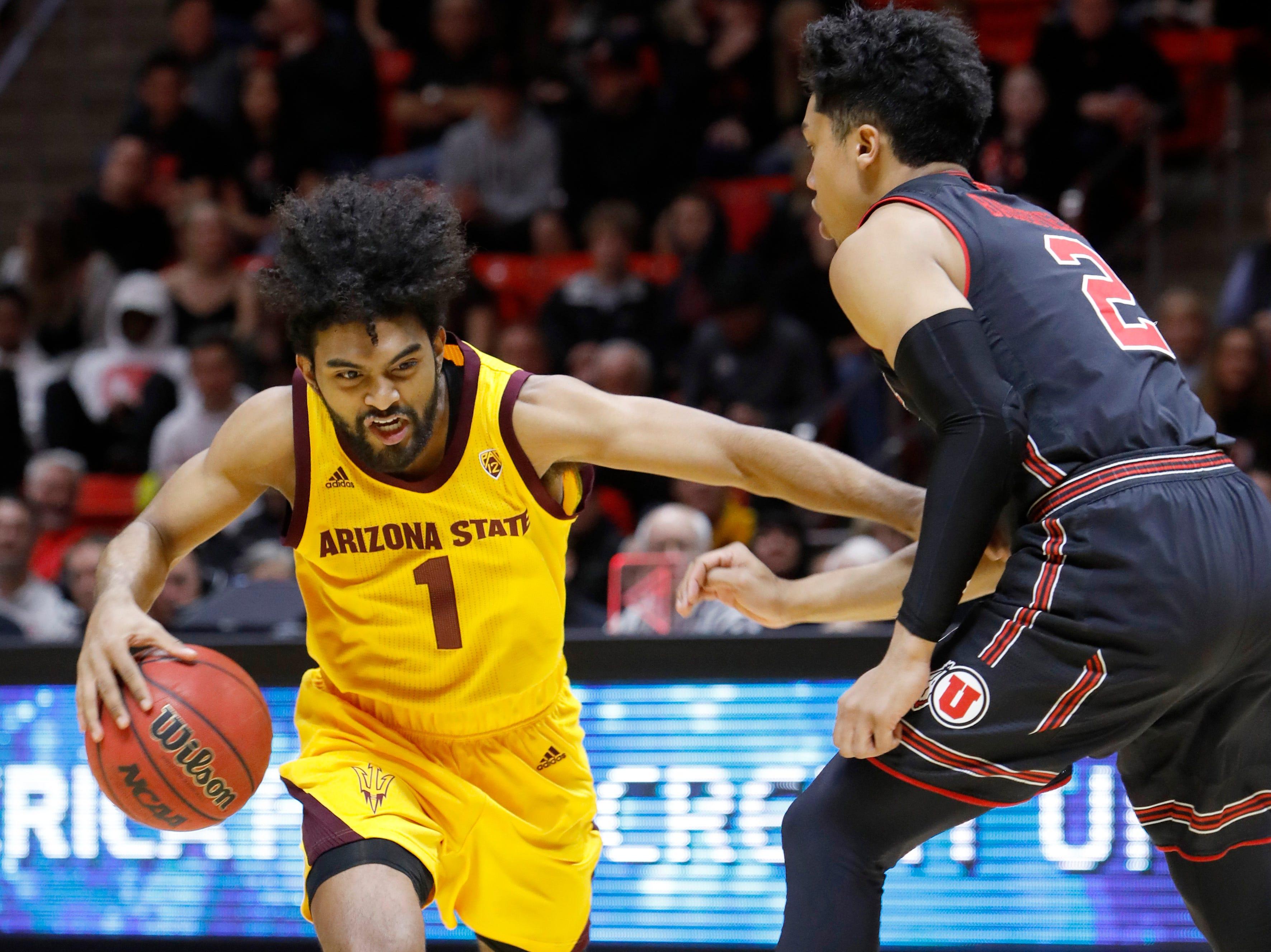Arizona State's Remy Martin (1) dribbles past Utah's Sedrick Barefield (2) during the first half of an NCAA college basketball game Saturday, Feb. 16, 2019, in Salt Lake City. (AP Photo/Kim Raff)