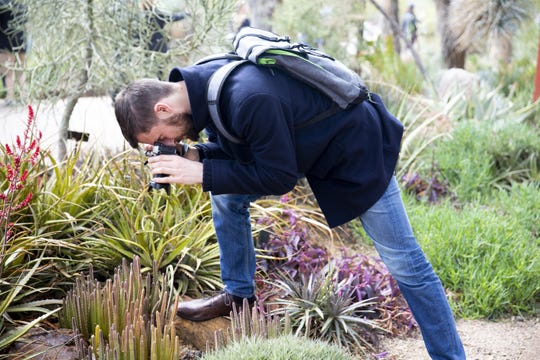 Christoph Gotz, who is visiting from Germany, takes a photo of patterns he finds in the plants at the Desert Botanical Garden 80th Anniversary Celebration on Saturday, Feb. 26, 2019.