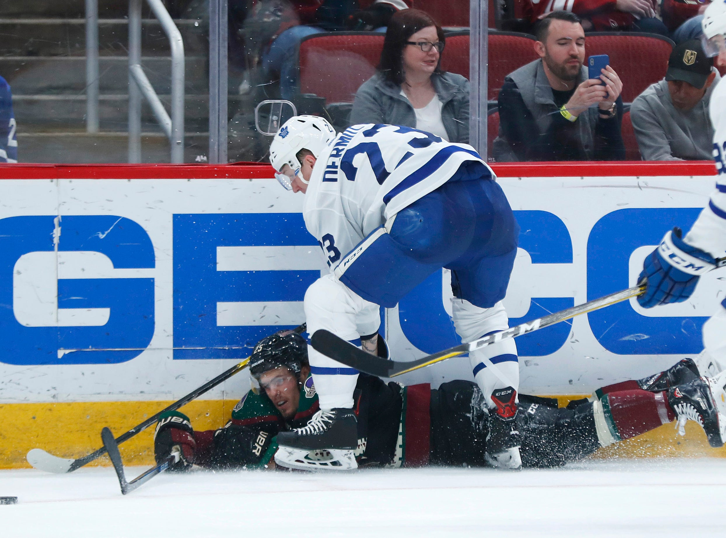 Maple Leafs' Travis Dermott (23) knocks Coyotes' Nick Cousins to the ice as he attempts to make a pass during the second period at Gila River Arena in Glendale, Ariz. on February 16, 2019.