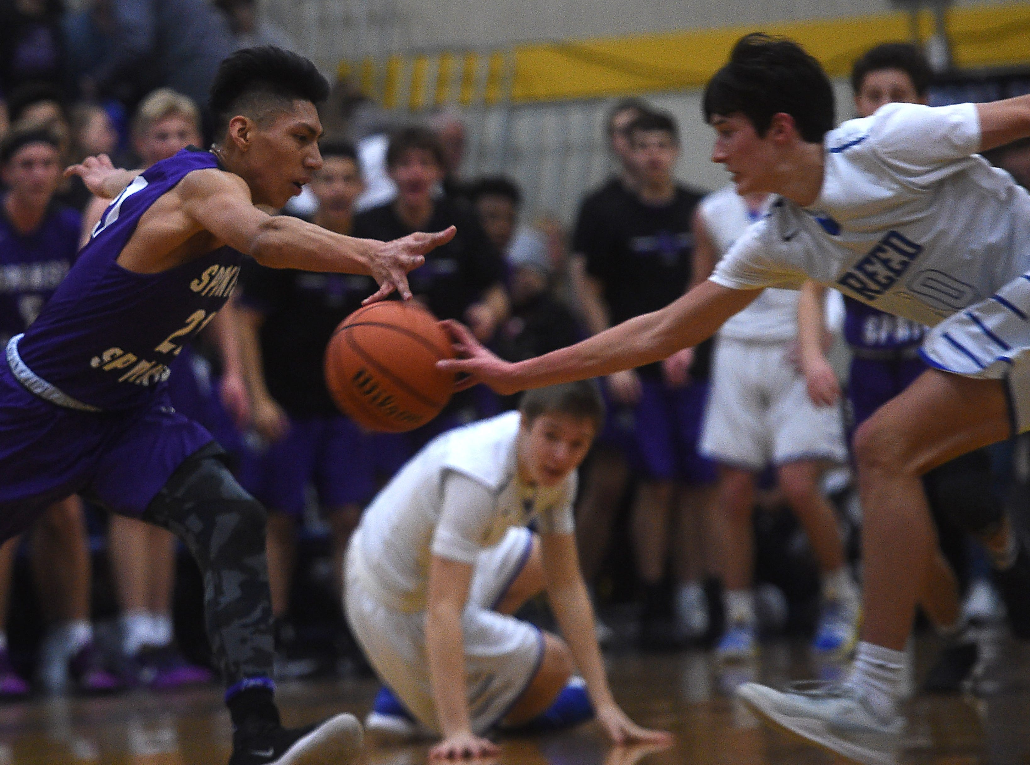 Reed's Trey Stevens (10) and Spanish Springs' Leo Grass reach for a loose ball during their basketball game in Sparks on Feb. 16, 2019.
