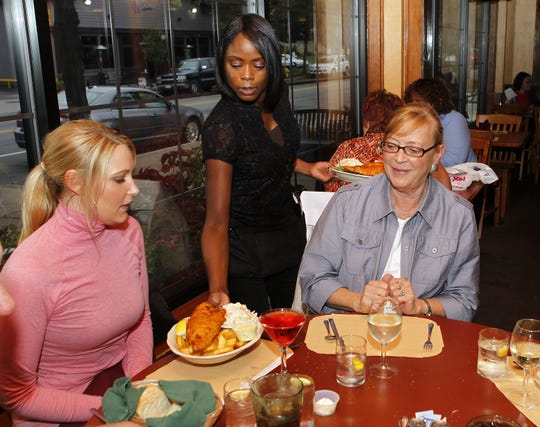 In this 2010 file photo, server Carolyn Hall of Lyons, serves up fish fries to Natalie Brown, of Greece, left, and her mother, Maggie Brown, of Webster, at the Winfield Grill.