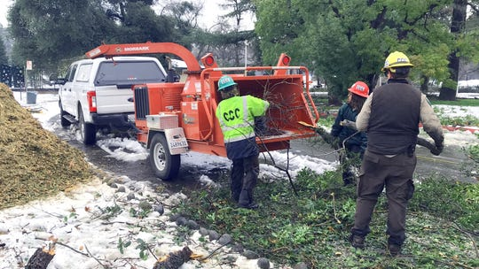 A crew from the Shasta-Cascade California Conservation Corps helps clear downed trees and broken-off limbs in Lake Redding Park on Thursday, Feb. 14, 2019, in the storm's aftermath.