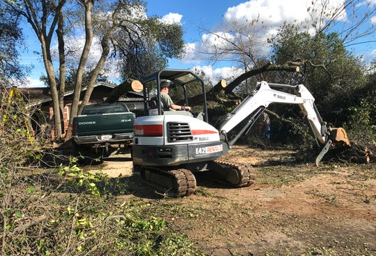 Karl Schreiber operates a Bobcat to remove branches and trees that fell outside his Traverse Street home early Wednesday morning in Redding. One of his trees landed on his Dodge Ram 1500 that was parked in the driveway during the snowstorm.