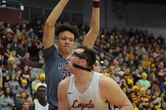 Loyola's Cameron Krutwig looks to go up for a shot with MSU's Darian Scott defending him.