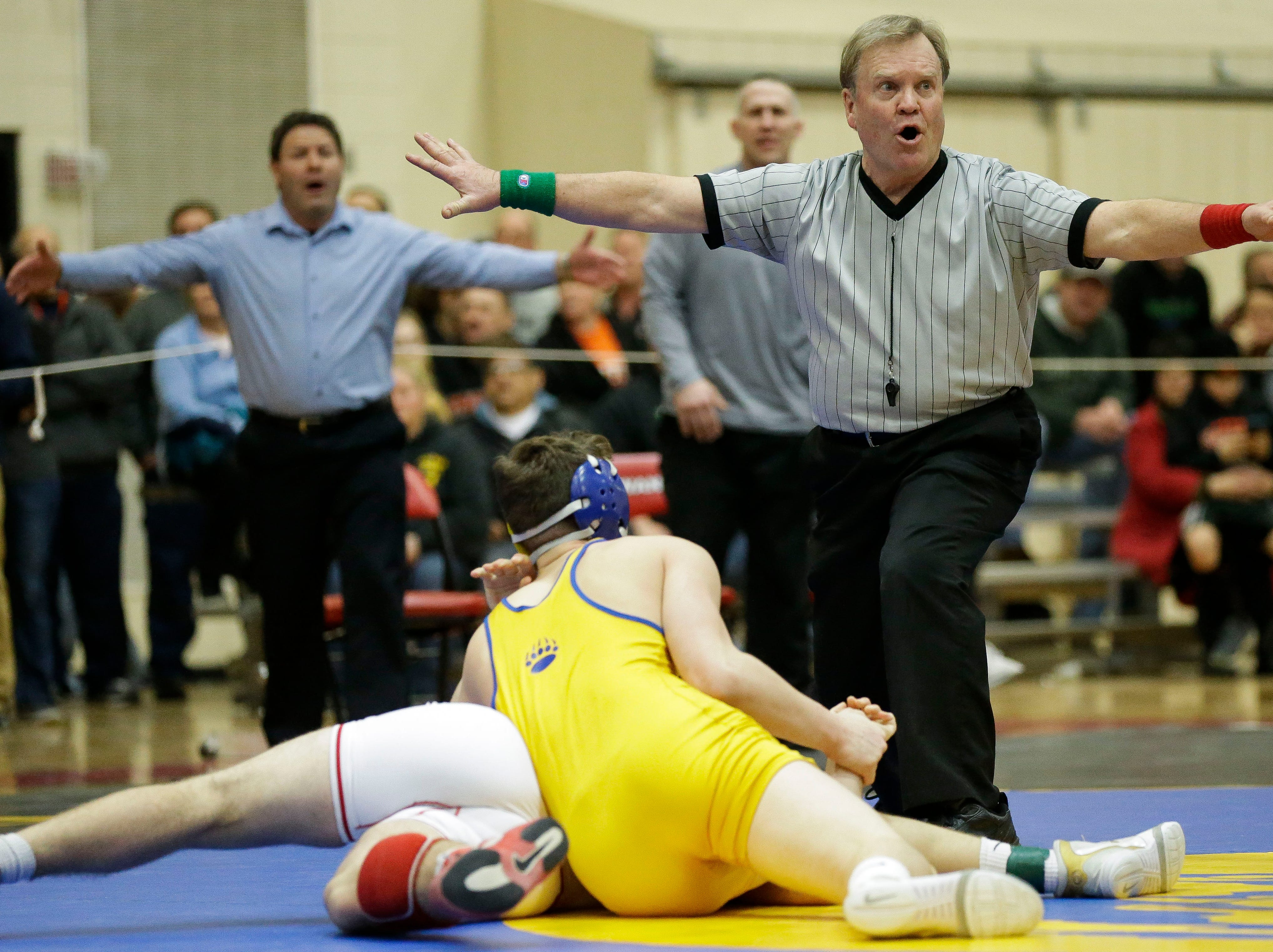 A referee gives a neutral signal in a 182-pound championship match on Saturday, February 16, 2019, during a Division 3 sectional meet at Shawano High School in Shawano, Wis.