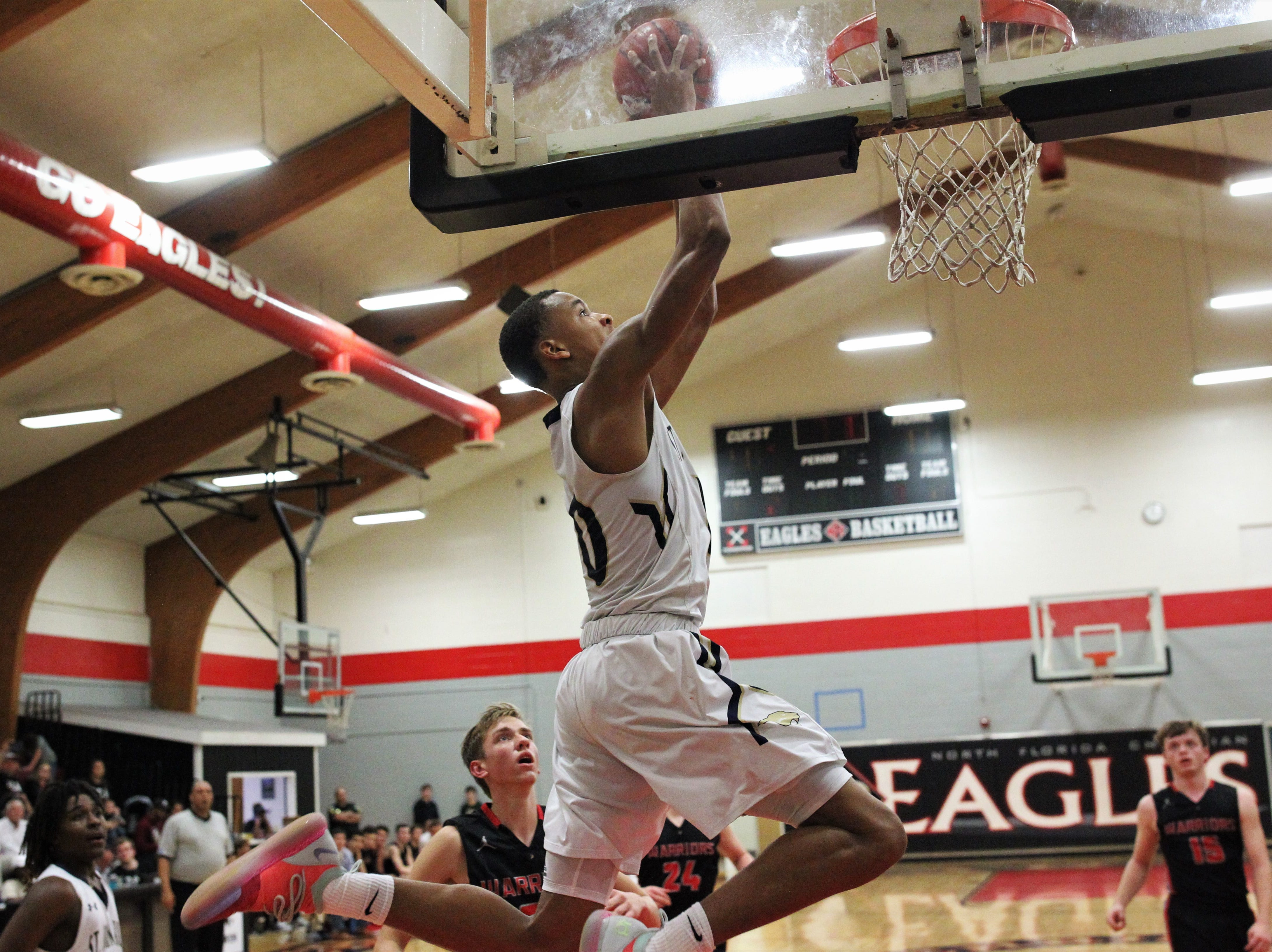 St. John Paul II forward Allan Jeanne-Rose catches an alley-oop dunk as St. John Paul II's boys basketball team captured a District 1-3A title by beating Pensacola Christian 85-51 at NFC on Feb. 16, 2019.
