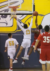 Santa Clara's Nick Abbott blocks the shot of Hueneme's Levante Boyd during Saturday's CIF-Southern Section Division 5AA semifinal at Santa Clara High. The host Saints won 51-37.