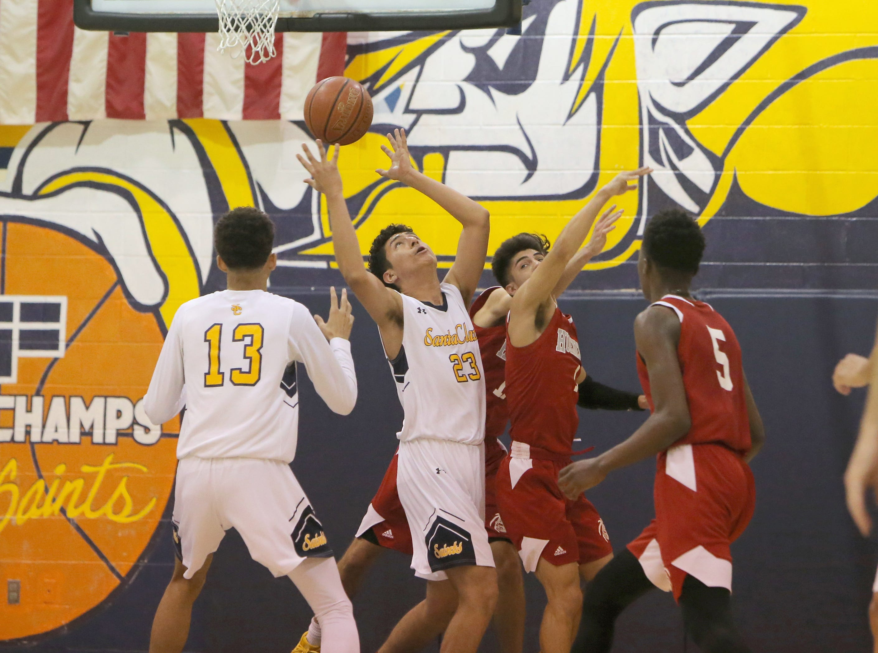 Santa Clara's Anthony Juarez, 23, battles Hueneme's Antonio Ayala for the rebound during Saturday's CIF-Southern Section Division 5AA semifinal at Santa Clara High. The host Saints won 51-37.