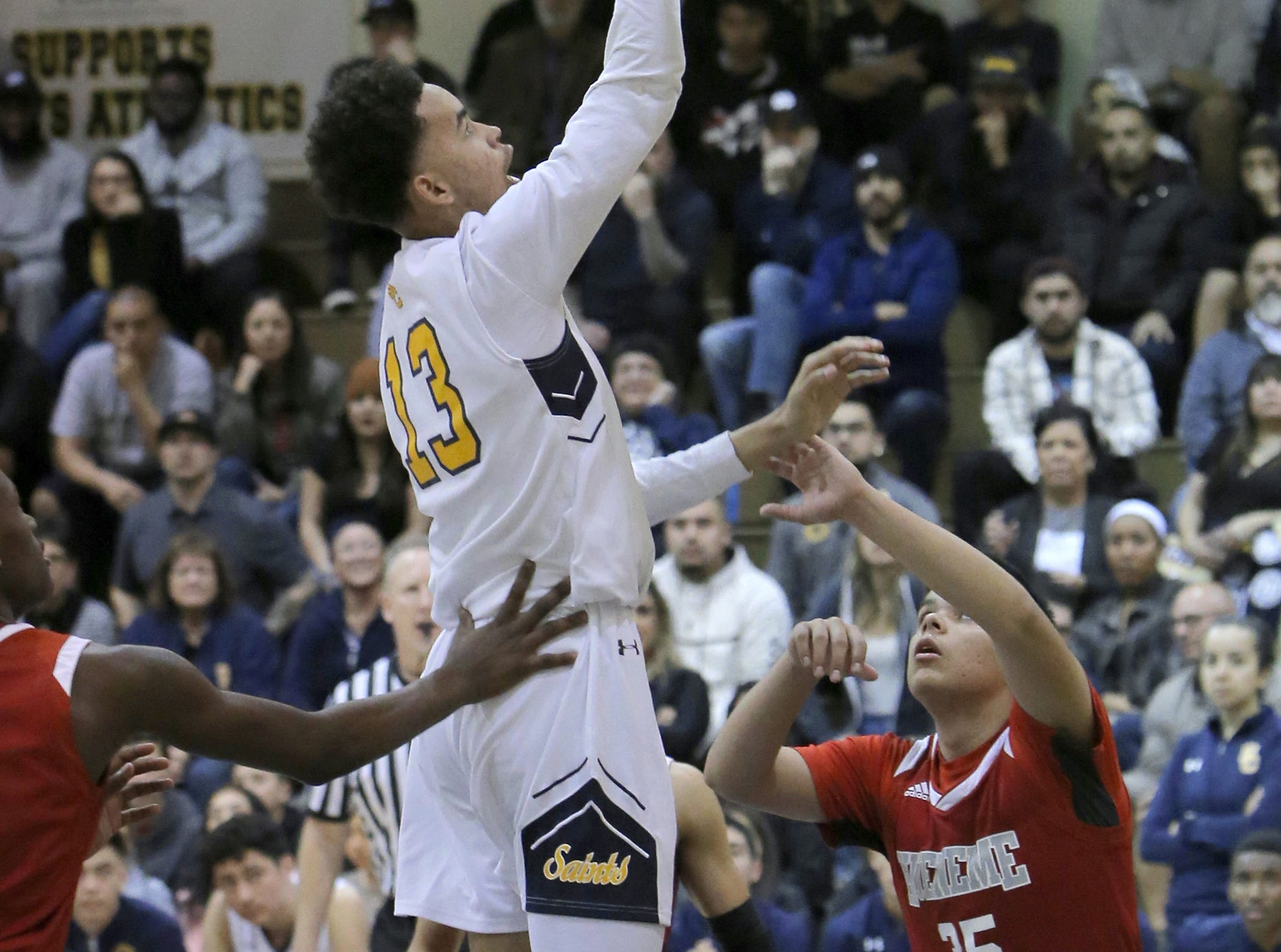 Santa Clara's Nick Abbott goes up for an easy two as Hueneme's Antonio Ayala, right, looks on during  Saturday's CIF-Southern Section Division 5AA semifinal at Santa Clara High. The host Saints won 51-37.