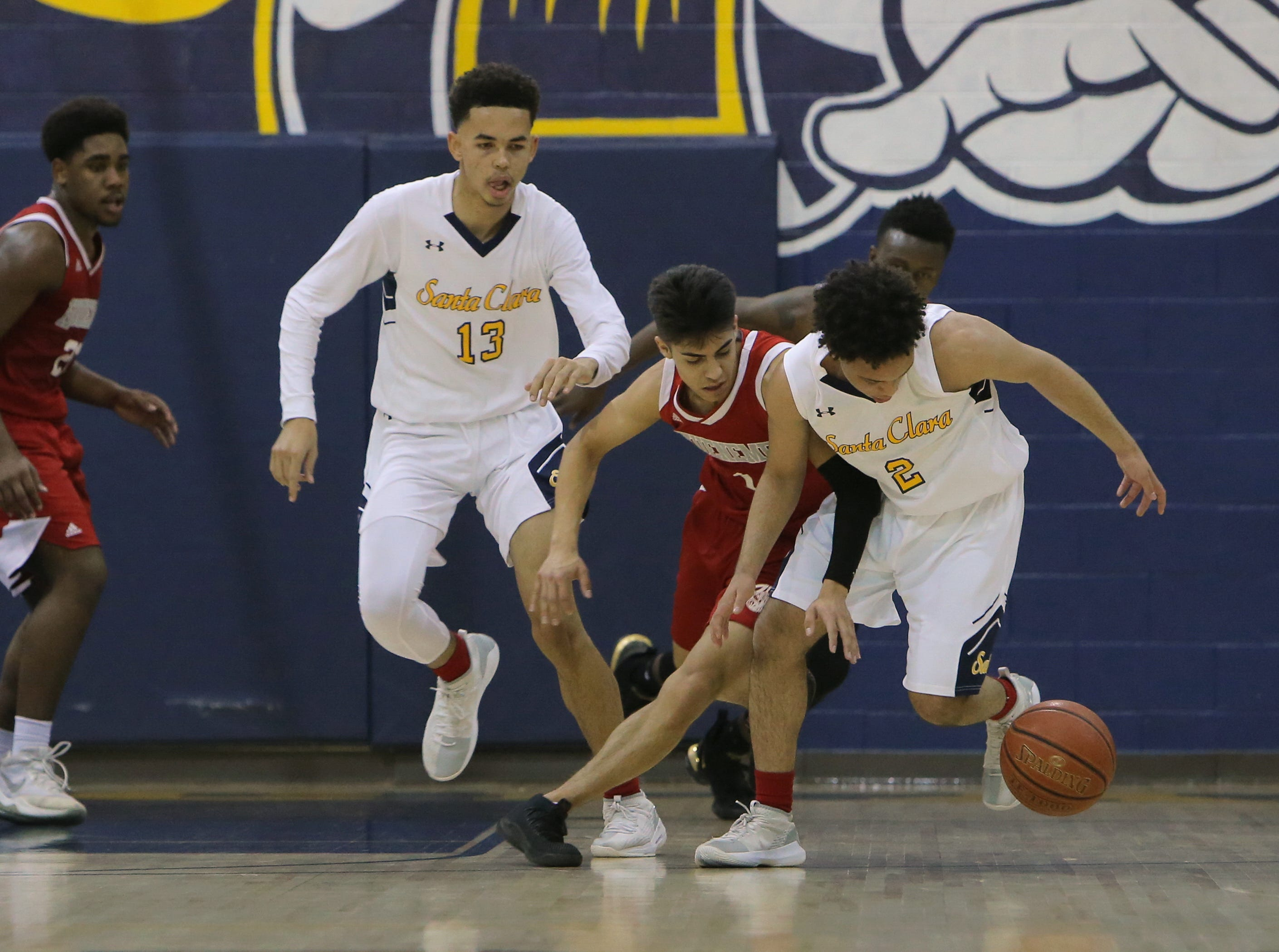 Santa Clara's Chris Mack, right, battles Hueneme's Antonio Ayala for the ball while Nick Abbott (13) looks on during  Saturday's CIF-Southern Section Division 5AA semifinal at Santa Clara High. The host Saints won 51-37.