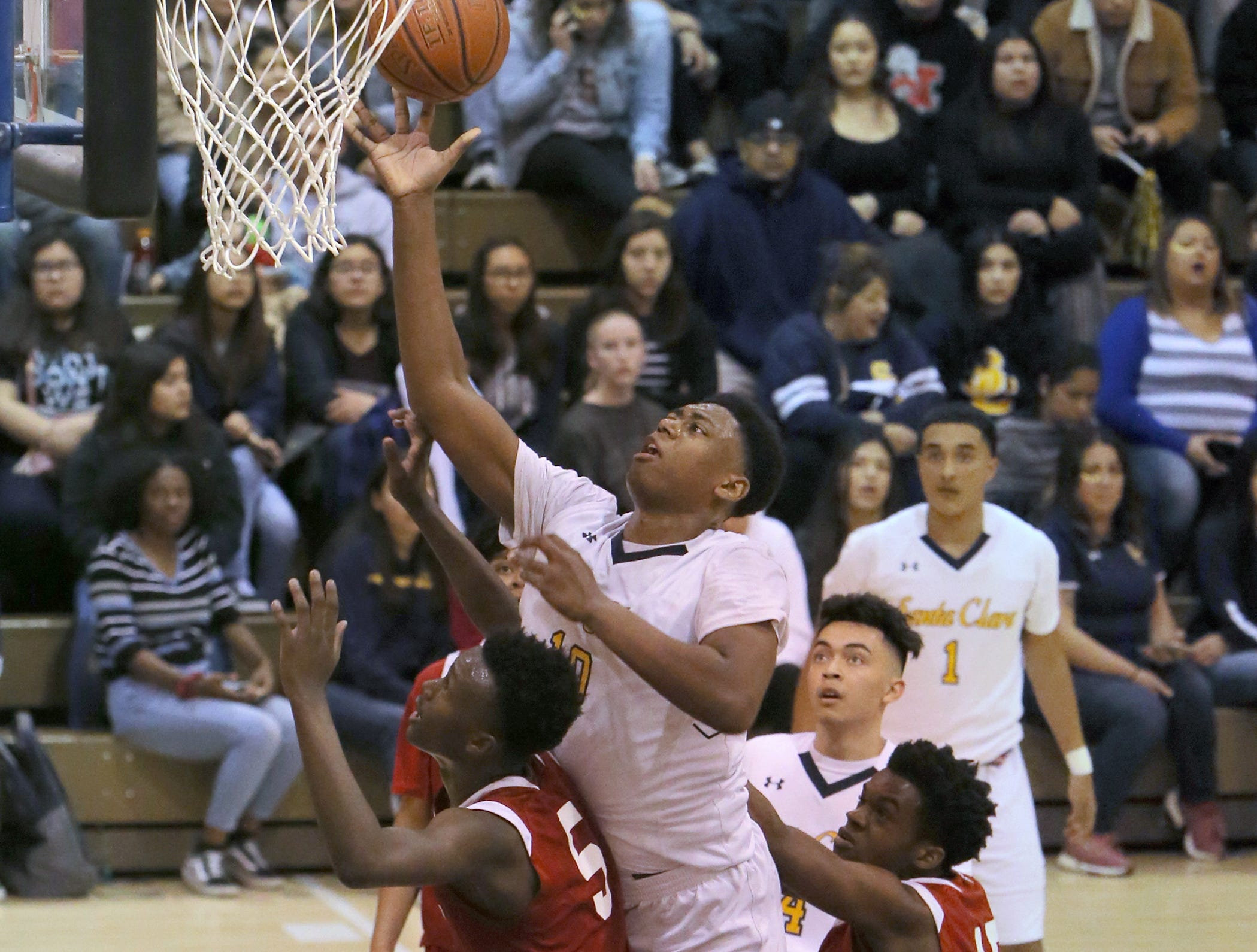 Santa Clara's Christian Oliver goes over Hueneme's Alex Asberry to score two of his 17 points during the Saints' 51-37 victory in a CIF-Southern Section Division 5AA semifinal Saturday night at Santa Clara High.