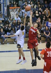 Hueneme's Antonio Ayala (1) and Santa Clara's Xavier Harvey both go for the rebound during Saturday's CIF-Southern Section Division 5AA semifinal at Santa Clara High. The host Saints won 51-37.