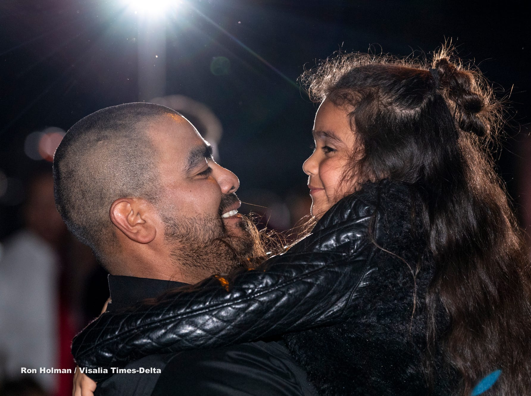 """Isaac Castro lifts his daughter Cambria Castro, 6, during the annual Father-Daughter Dance at the Visalia Convention Center on Saturday, February 16, 2019. This year's theme was """"Masquerade Ball,"""" and included music, dancing and refreshments."""