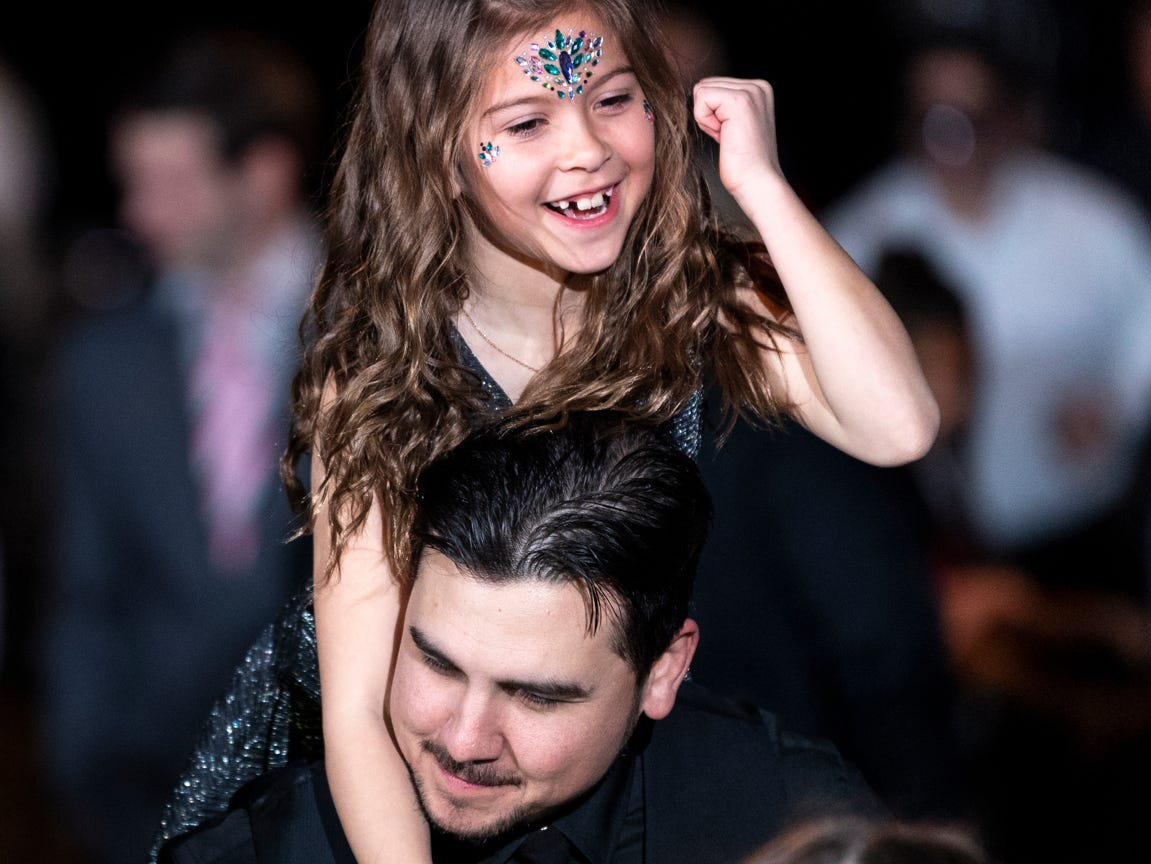 """Emily Moreno, 8, dances atop the shoulders of her father Andrew Moreno during the annual Father-Daughter Dance at the Visalia Convention Center on Saturday, February 16, 2019. This year's theme was """"Masquerade Ball,"""" and included music, dancing and refreshments."""