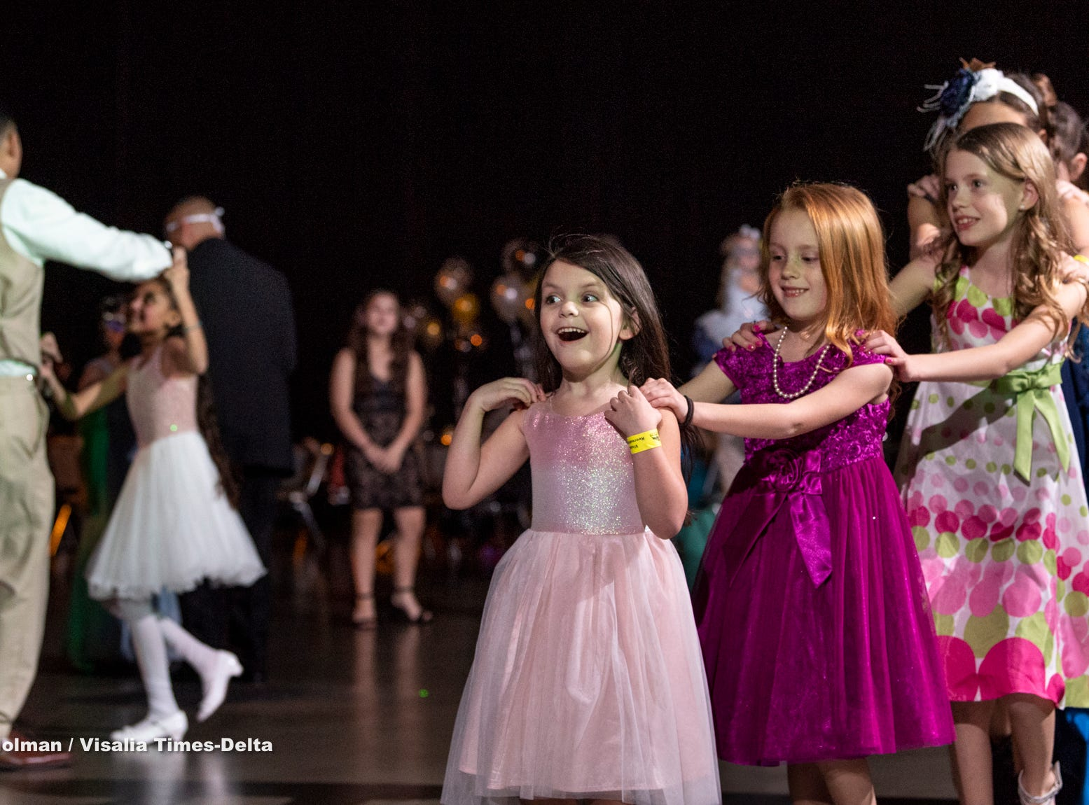 """Olivia Caudle, 4, leads others girls around the dance floor during the annual Father-Daughter Dance at the Visalia Convention Center on Saturday, February 16, 2019. This year's theme was """"Masquerade Ball,"""" and included music, dancing and refreshments."""