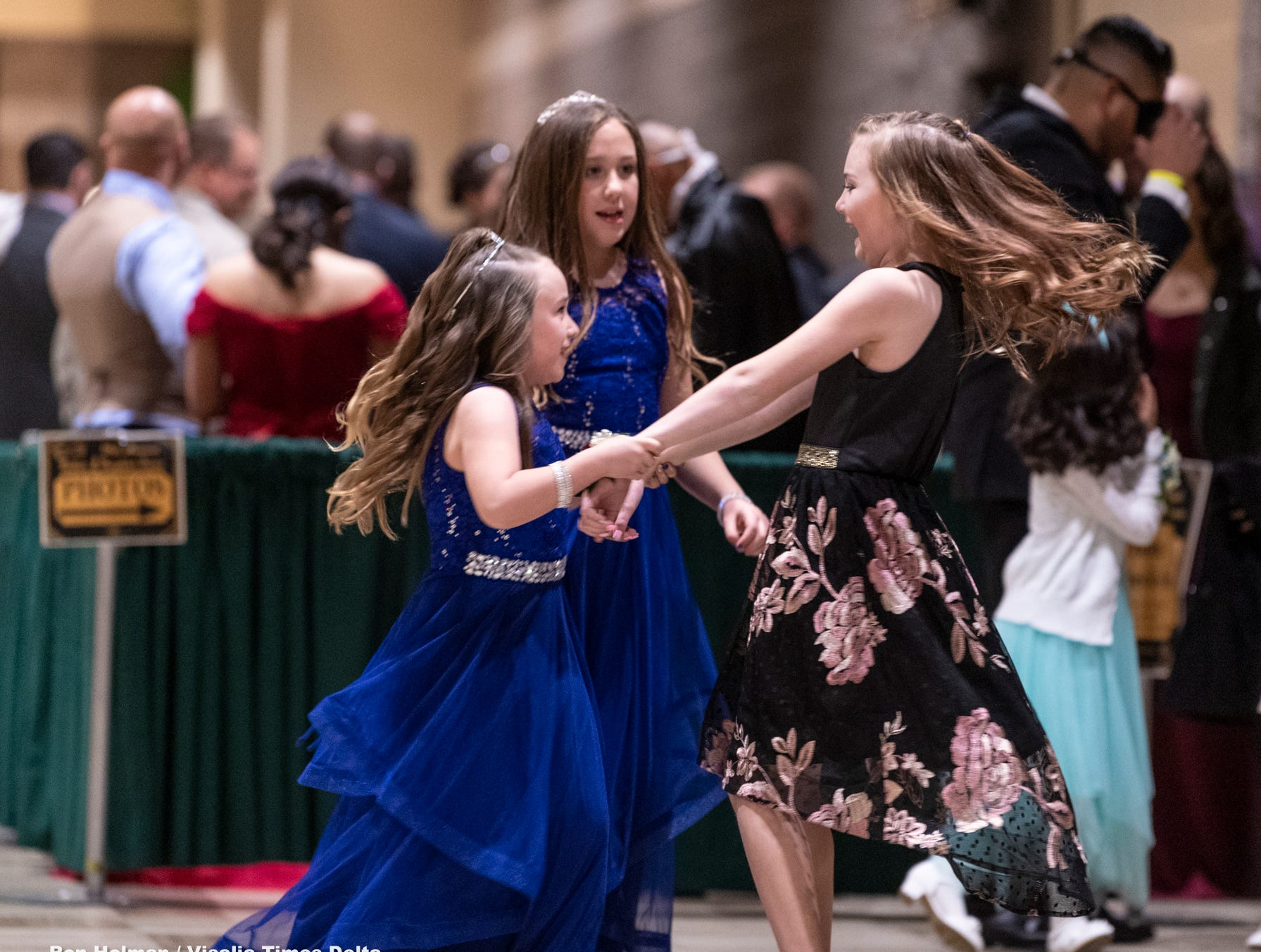 """Corrina Wilson, 7, left, Brooklyn Robles, 10, and Brooke Knauter, 9, dance in anticipation of the annual Father-Daughter Dance at the Visalia Convention Center on Saturday, February 16, 2019. This year's theme was """"Masquerade Ball,"""" and included music, dancing and refreshments."""